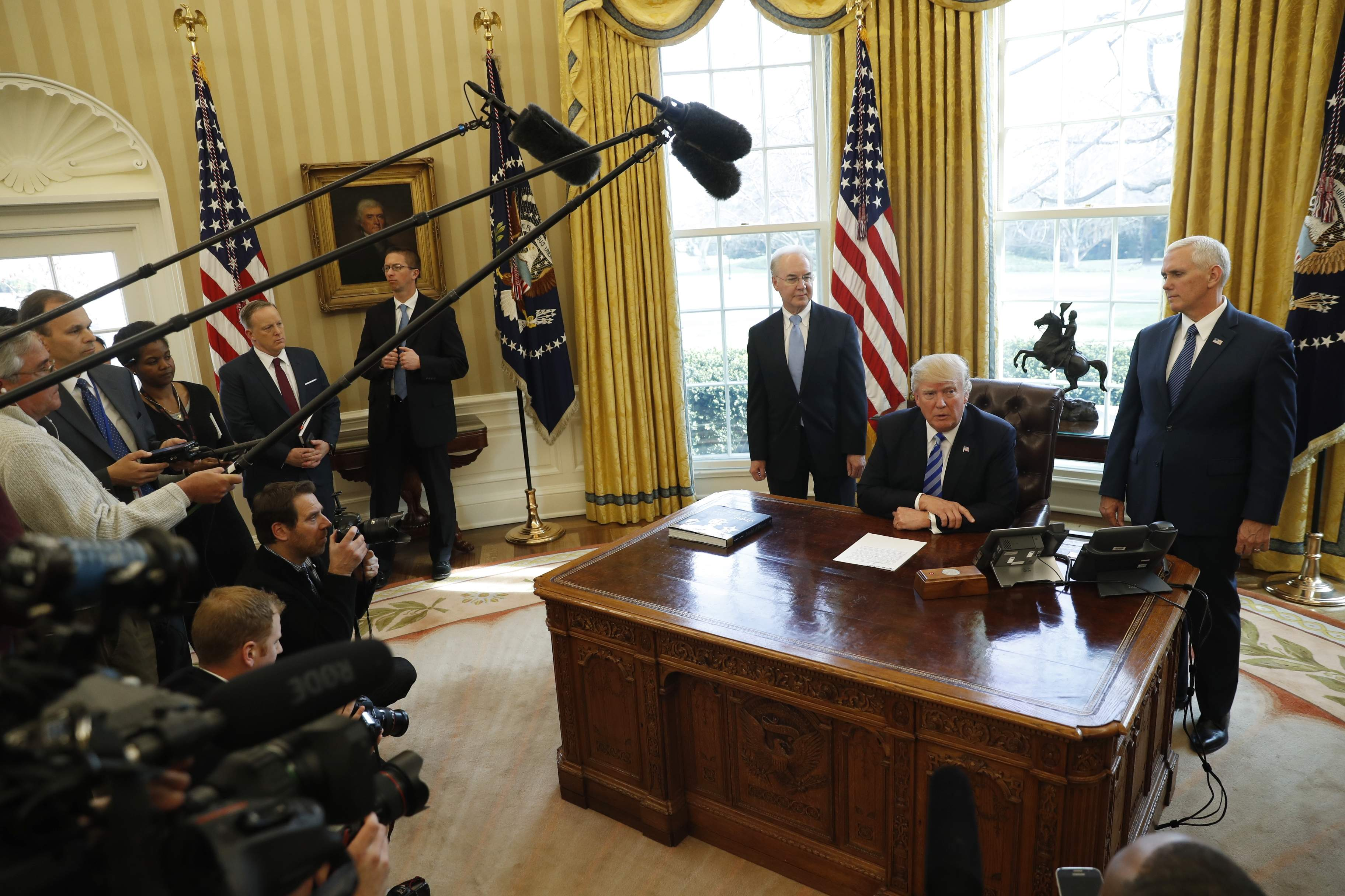DAY 64 - In this March 24, 2017, file photo, President Donald Trump, flanked by Health and Human Services Secretary Tom Price, left, and Vice President Mike Pence, meets with members of the media regarding the health care overhaul bill in the Oval Office of the White House in Washington. (AP Photo/Pablo Martinez Monsivais, File)