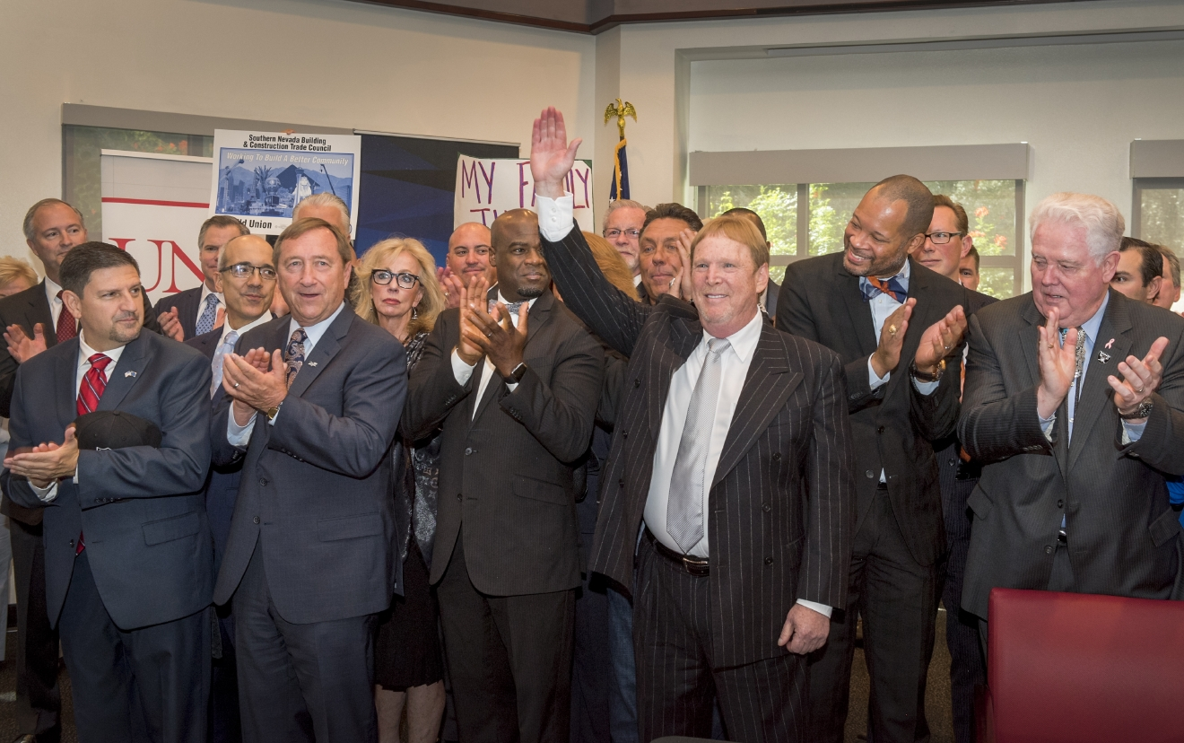 Oakland Raiders owner Mark Davis, third from right, waves to fans after joining Nevada legislators as they wait for Nevada Gov. Brian Sandoval to sign Senate Bill 1 into law in a ceremony in UNLV's Tam Alumni Hall on Monday, Oct. 17, 2016. Senate Bill 1 authorizes the funds for the Las Vegas Convention Center District expansion as well as the construction of a 65,000 seat NFL footbal stadium. LVCVA President and CEO Rossi Ralenkotter is second from left. (Mark Damon/Las Vegas News Bureau)