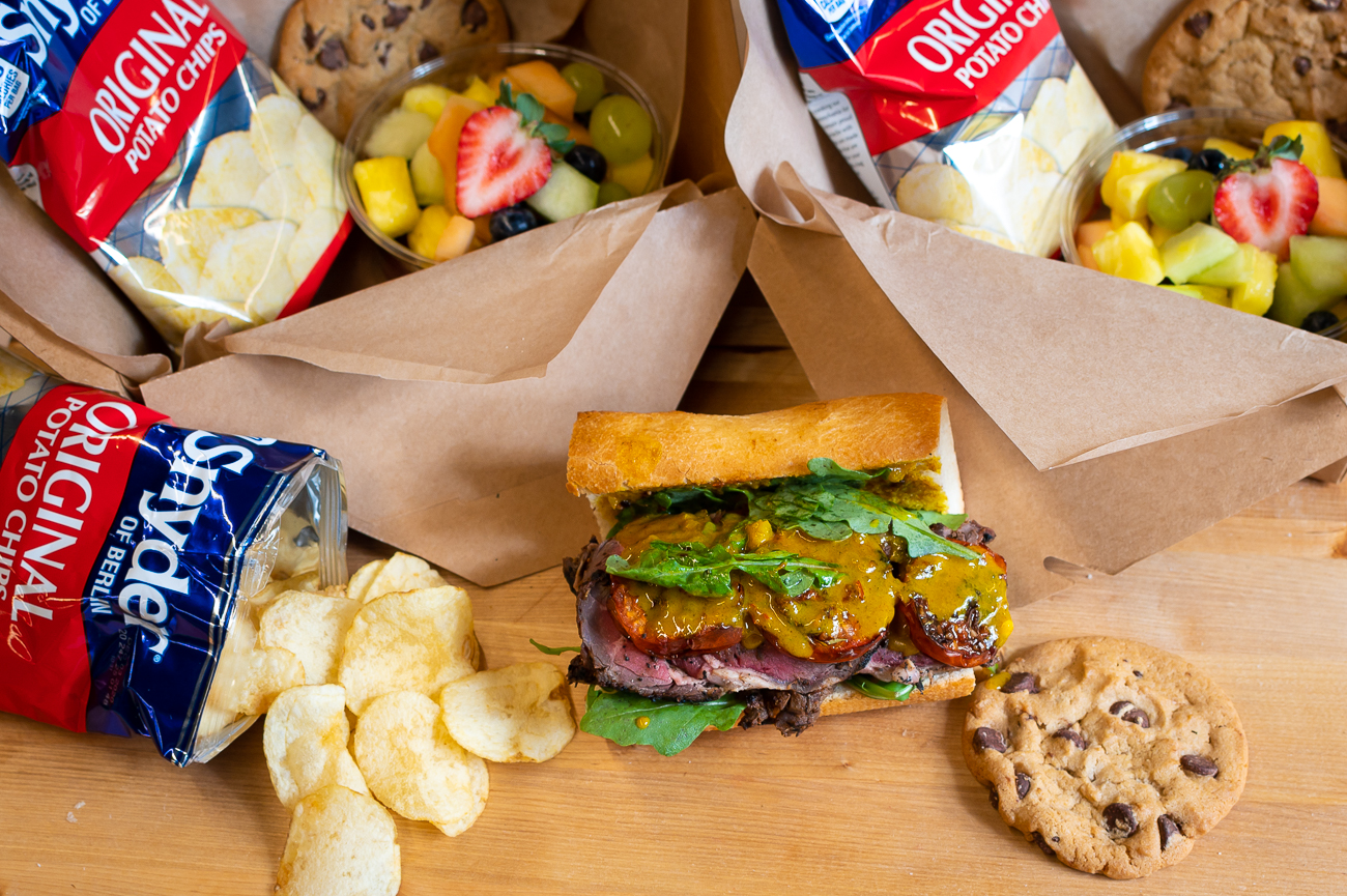 Their boxed lunches are available through the end of the year. Pictured: spice-rubbed roast beef, roasted tomatoes, and a curry chutney on French bread. Each boxed lunch comes with a bagged snack, cookie, and fruit salad. / Image: Phil Armstrong, Cincinnati Refined // Published: 11.6.20
