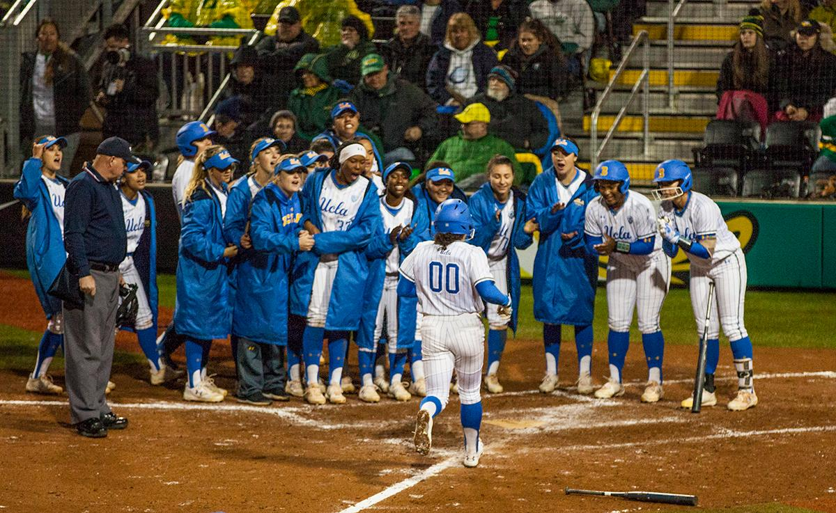 The UCLA Bruins Rachel Garcia (#00) is welcomed into home plate by her team after hitting a two-run homer. The University of Oregon Ducks softball pitcher Miranda Elish held the UCLA Bruins scoreless for five innings as the Ducks put seven runs on the board. The Bruins rallied with a two-run homer in the sixth and a three-run home run in the seventh, but the Ducks held on and beat undefeated UCLA 7-5 at Jane Sanders Stadium Saturday. The Ducks improved their record to 24-5. Photo by William Tierney, Oregon News Lab