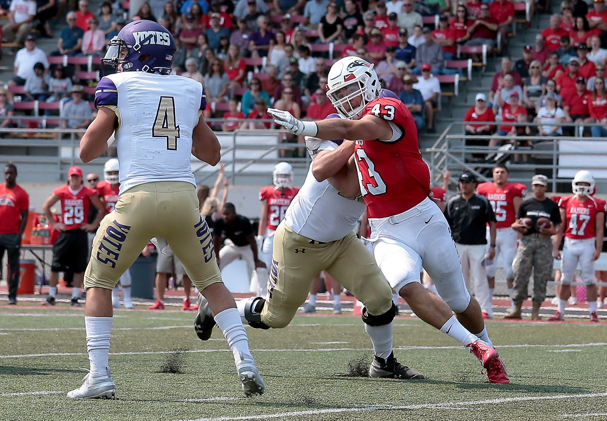 Larry Stauth Jr./For the Daily Tidings<br>Southern Oregon University senior defensive end Sean Rogers races after College of Idaho quarterback Darius-James Peterson at Raider Stadium on Saturday.