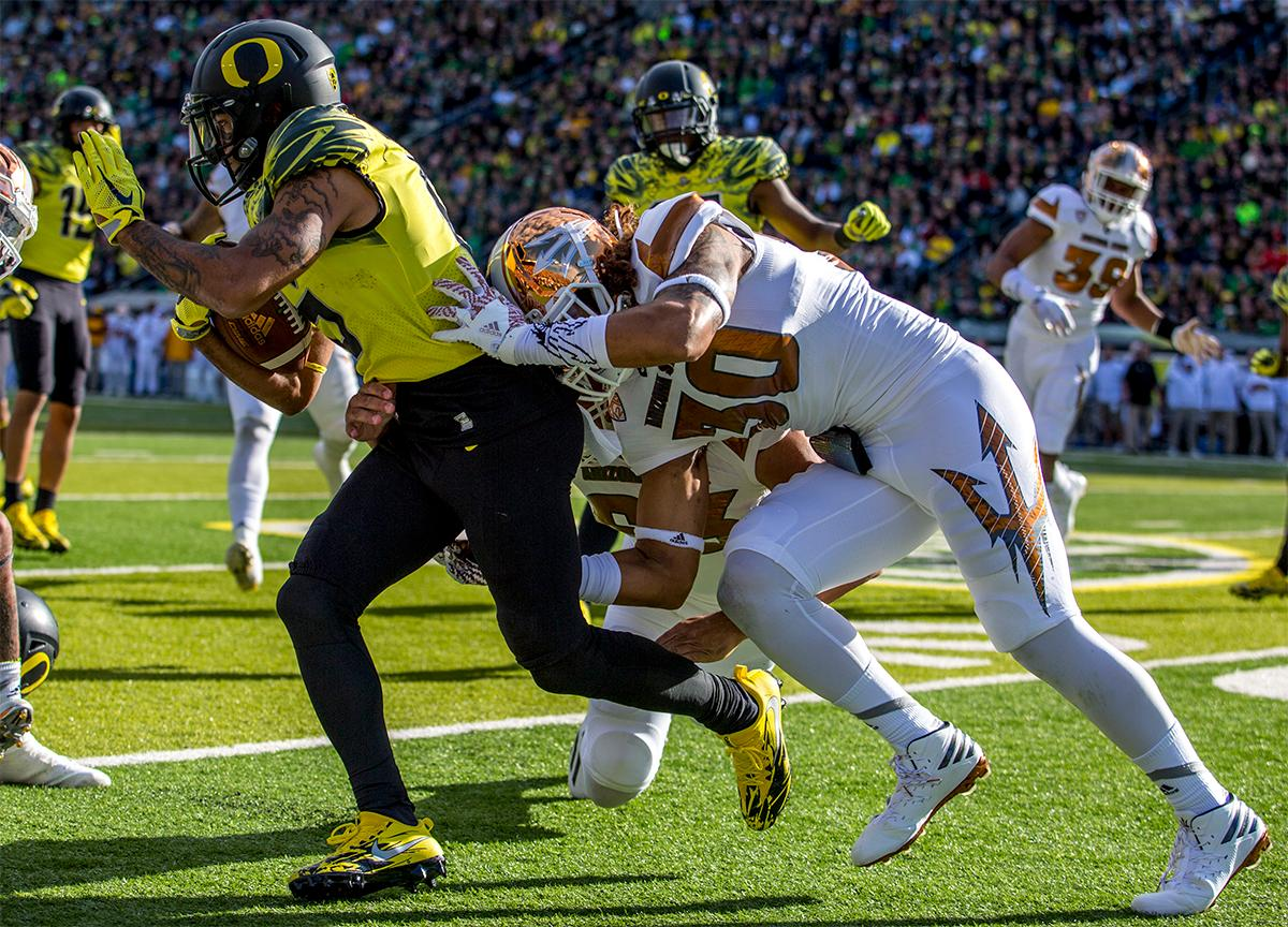 The Duck's Charles Nelson (#6) moves the ball down the field as a Sun Devils player pushes him out of bounds. Oregon lead at the end of the 1st half 30-14. Photos by August Frank, Oregon News Lab