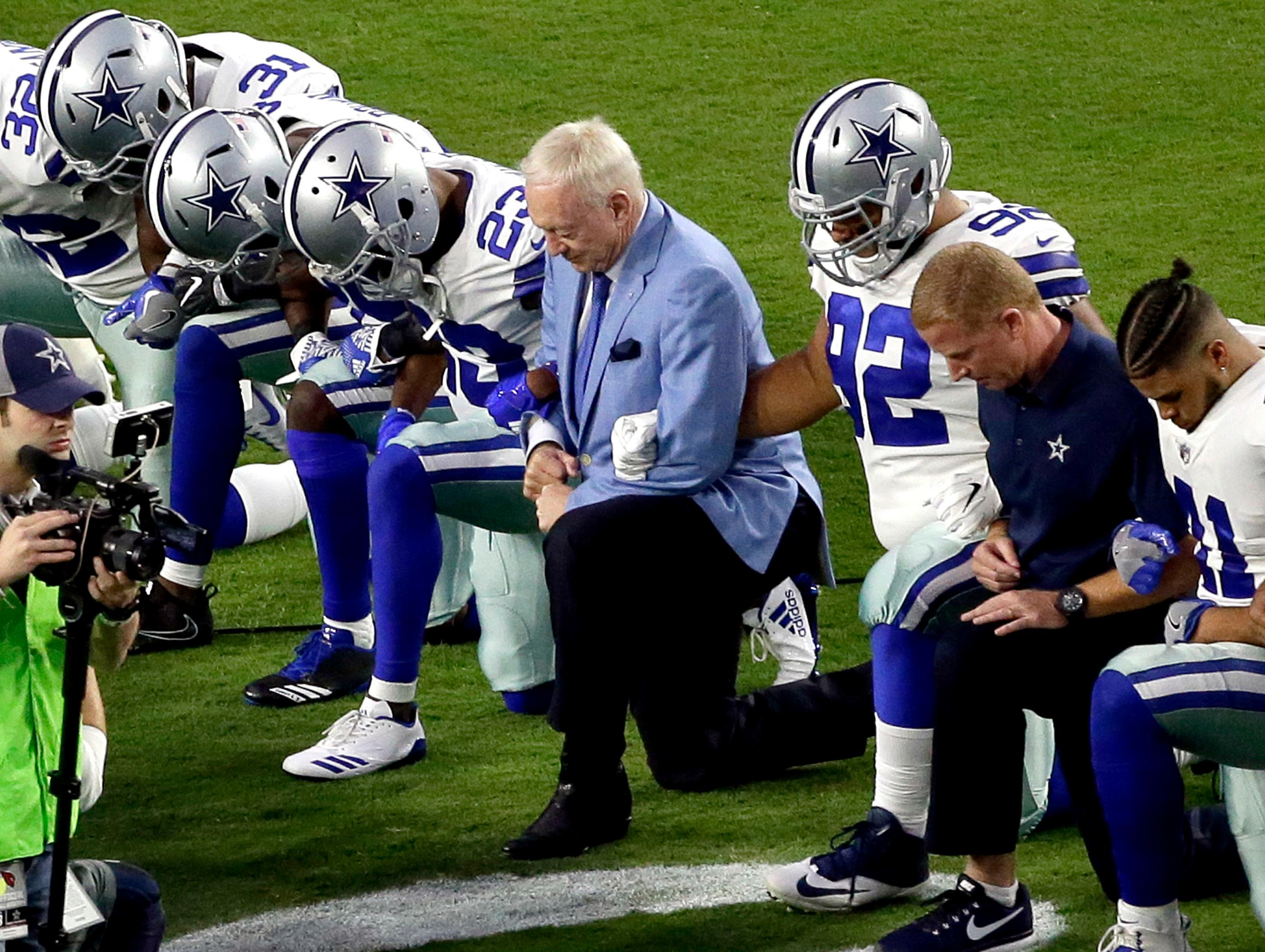 "FILE - In this Monday, Sept. 25, 2017, file photo, the Dallas Cowboys, led by owner Jerry Jones, center, take a knee prior to the national anthem and an NFL football game against the Arizona Cardinals, in Glendale, Ariz. ESPN anchor Jemele Hill has been suspended by the network for two weeks for making political statements on social media.  Hill, who is African-American, received criticism from the network last month after referring to President Donald Trump as a ""white supremacist.""  On Monday, Oct. 9, 2017, Hill targeted Jerry Jones, after the Dallas Cowboys owner stated that players who disrespect the flag would not play for his team.  (AP Photo/Matt York, File)"