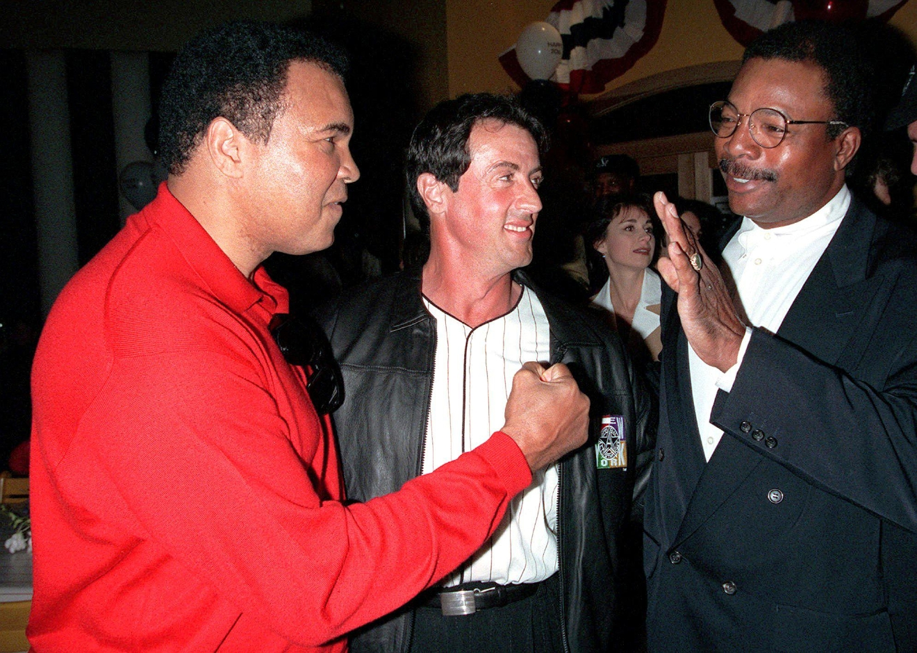 "FILE – In this March 16, 1996, file photo, former heavyweight boxing champion Muhammad Ali, left, joins actor and screenwriter Sylvester Stallone, center, and Stallone's ""Rocky"" co-star, former professional football player Carl Weathers, right, to mark the 20th anniversary of the movie ""Rocky"" during a party in New York. Four decades after the Nov. 21, 1976, premiere of ""Rocky,"" the movie's reach is international, and the title character's underdog tale of determination, grit and sleepy-eyed charm still resonates with fans. (AP Photo/Albert Ferreira, File)"