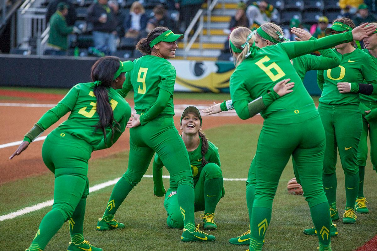 The Ducks (from left: DJ Sanders #37, Shannon Rhodes #9, Lauren Lindvall #8, April Utecht #6) have fun before their game against UCLA on Saturday. The University of Oregon Ducks softball pitcher Miranda Elish held the UCLA Bruins scoreless for five innings as the Ducks put seven runs on the board. The Bruins rallied with a two-run homer in the sixth and a three-run home run in the seventh, but the Ducks held on and beat undefeated UCLA 7-5 at Jane Sanders Stadium Saturday. The Ducks improved their record to 24-5. Photo by William Tierney, Oregon News Lab