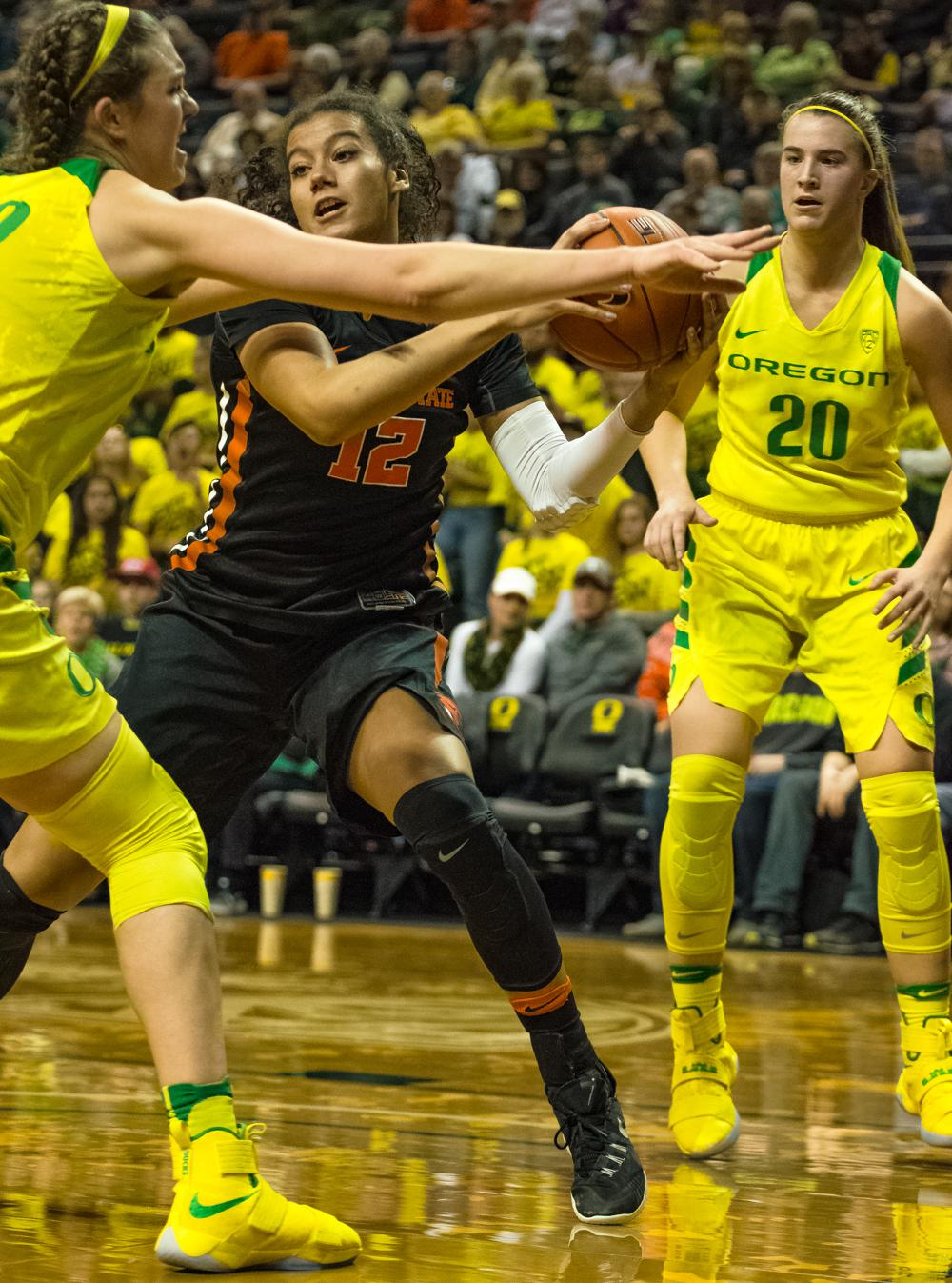 Oregon Ducks Forward Sierra Campisano (#52) defends against Oregon State Forward Kolbie Orum (#12) to stop the easy pass. Oregon Ducks lost 40-43 to Oregon State Beavers in a tightly matched fourth quarter. Photo by Jonathan Booker, Oregon News Lab