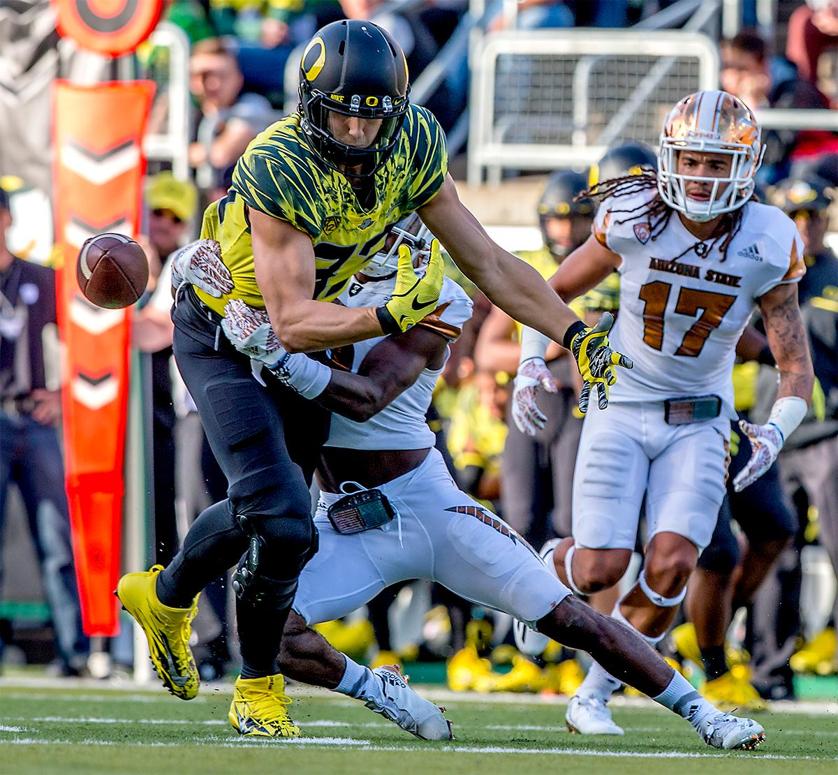 The Duck's Johnny Mundt (#83) watches the ball fly past him as he is taken out while trying to make a catch. The Oregon Ducks broke their losing streak by defeating the ASU Sun Devils on Saturday 54-35. Photo by August Frank, Oregon News Lab