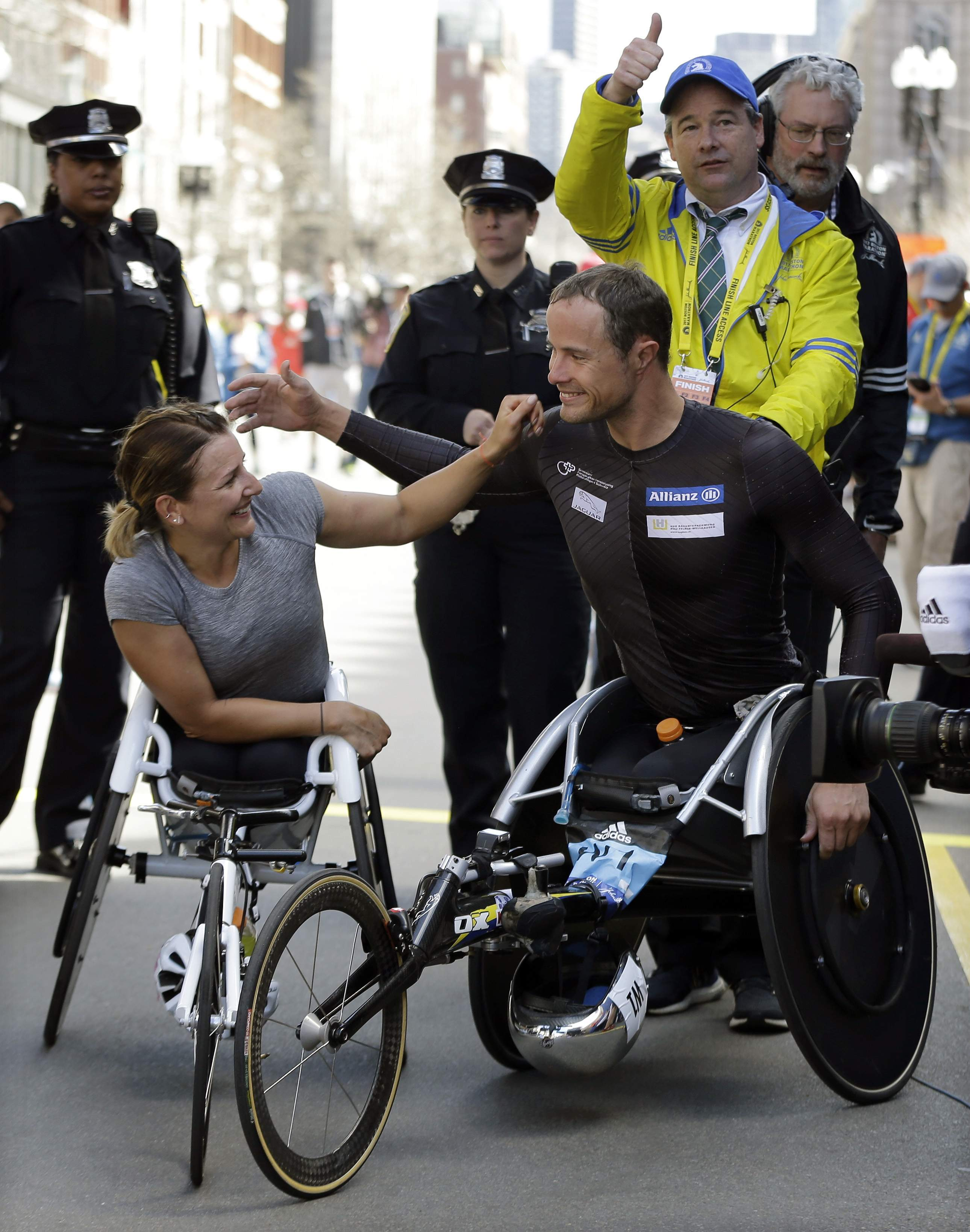 Wheelchair division winners Manuela Schar, left, and Marcel Hug, both of Switzerland, celebrate their wins in the 121st Boston Marathon on Monday, April 17, 2017, in Boston. THE ASSOCIATED PRESS