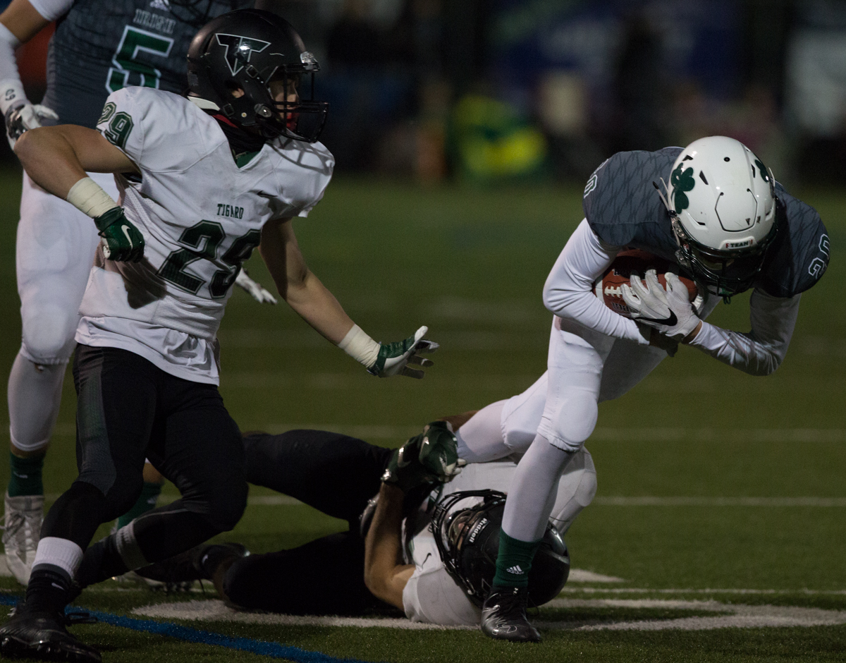Sheldon Irish wide receiver Jared Brabham (#20) is dragged down by a Tigard defender.  The Tigard Tigers defeated Sheldon 27-0 to advance to the OSAA 6A semifinals.  Photo by Austin Hicks, Oregon News Lab