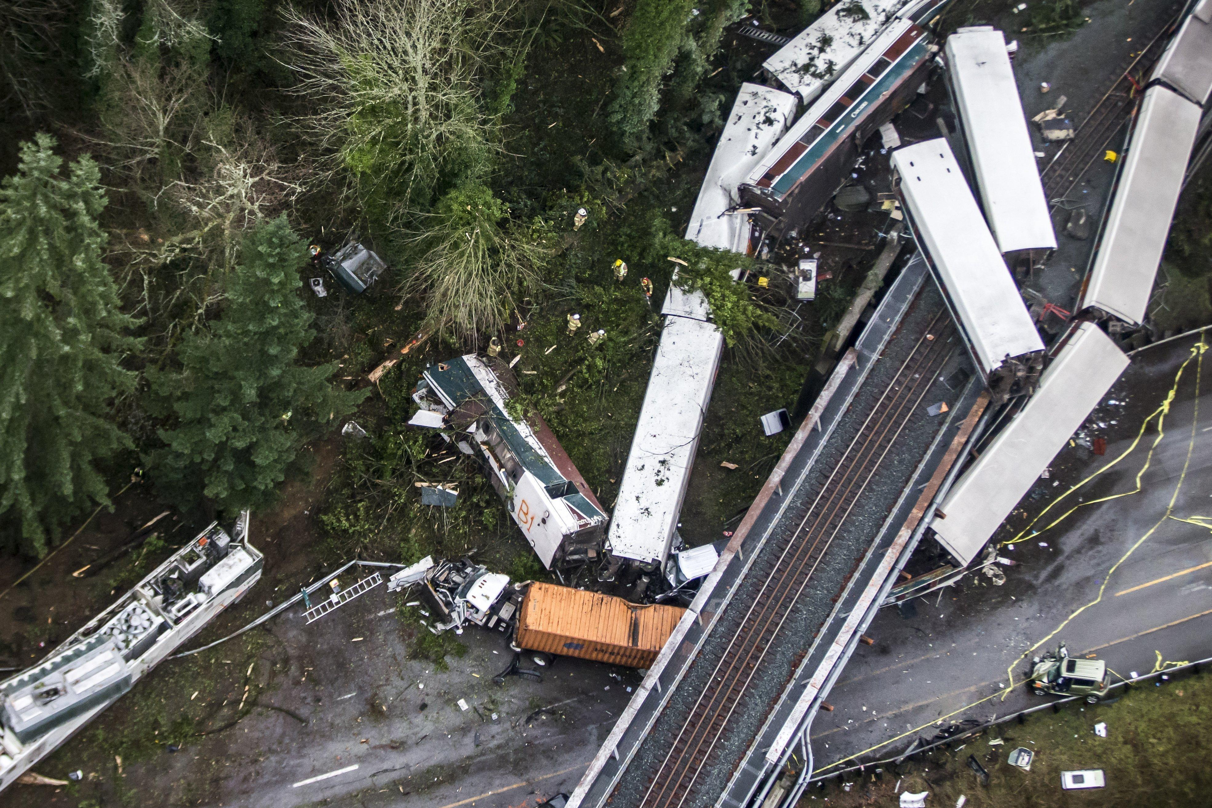 Cars from an Amtrak train that derailed above lie spilled onto Interstate 5, Monday, Dec. 18, 2017, in DuPont, Wash. The Amtrak train making the first-ever run along a faster new route hurtled off the overpass Monday near Tacoma and spilled some of its cars onto the highway below, killing several people, authorities said. (Bettina Hansen/The Seattle Times via AP)