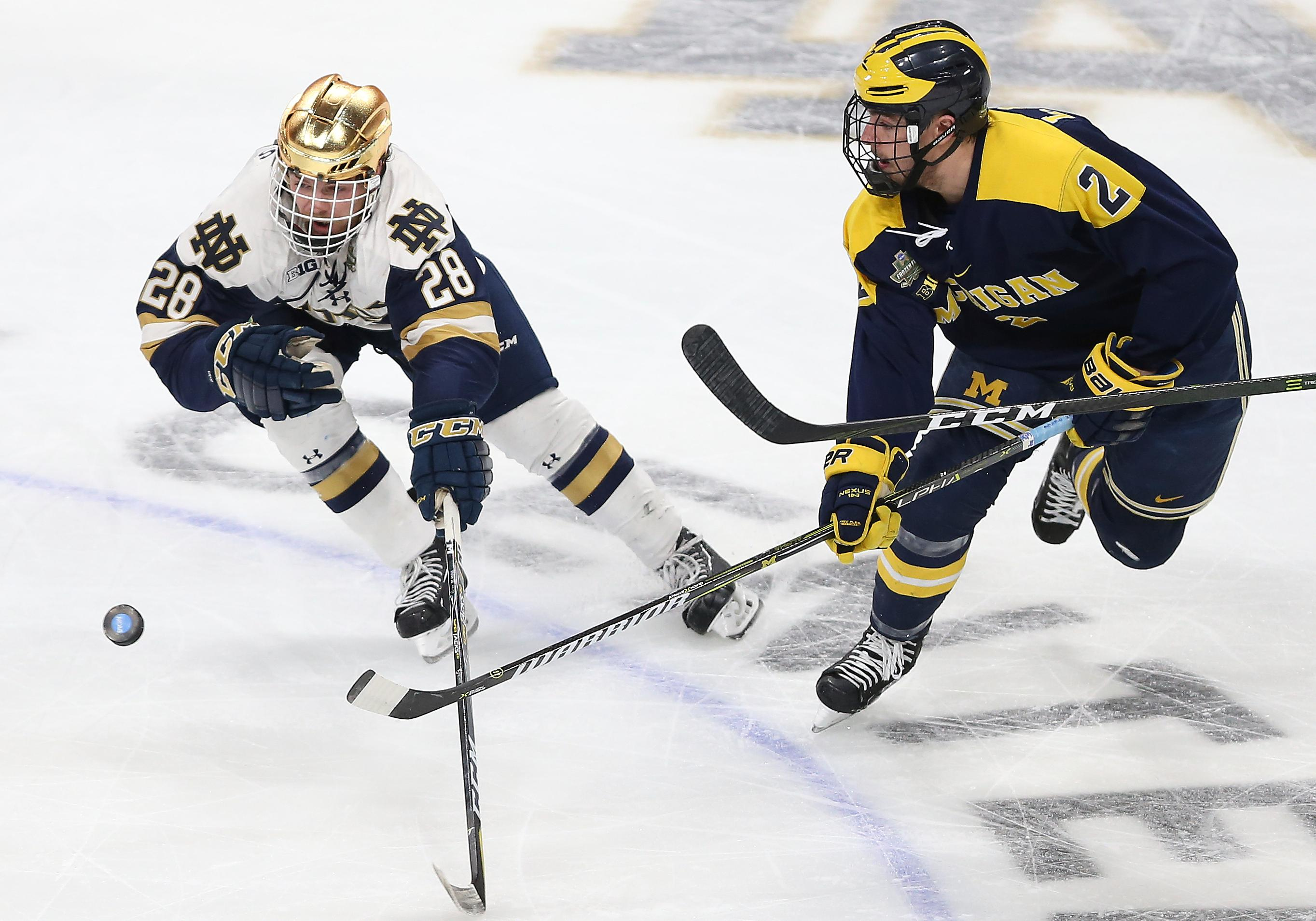 Notre Dame's Bo Brauer (28) reaches for the puck in front of Michigan's Luke Martin (2) during the second period of a semifinal in the NCAA men's Frozen Four college hockey tournament Thursday, April 5, 2018, in St. Paul, Minn. (AP Photo/Stacy Bengs)