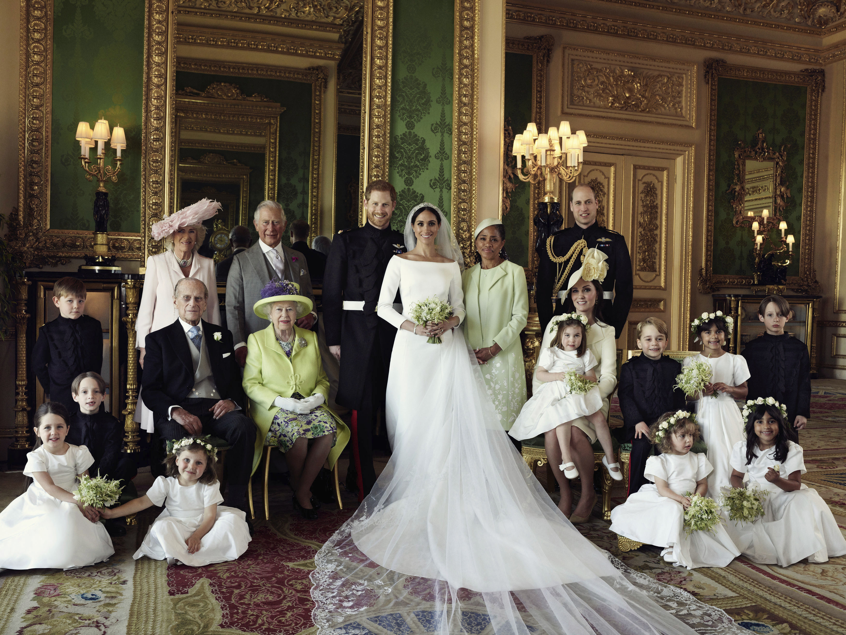 In this photo released by Kensington Palace on Monday May 21, 2018, shows an official wedding photo of Britain's Prince Harry and Meghan Markle, center, in Windsor Castle, Windsor, England, Saturday May 19, 2018. Others in photo from left, back row, Jasper Dyer, Camilla, Duchess of Cornwall, Prince Charles, Doria Ragland, Prince William; center row, Brian Mulroney, Prince Philip, Queen Elizabeth II, Kate, Duchess of Cambridge, Princess Charlotte, Prince George, Rylan Litt, John Mulroney; front row, Ivy Mulroney, Florence van Cutsem, Zalie Warren, Remi Litt. (Alexi Lubomirski/Kensington Palace via AP)
