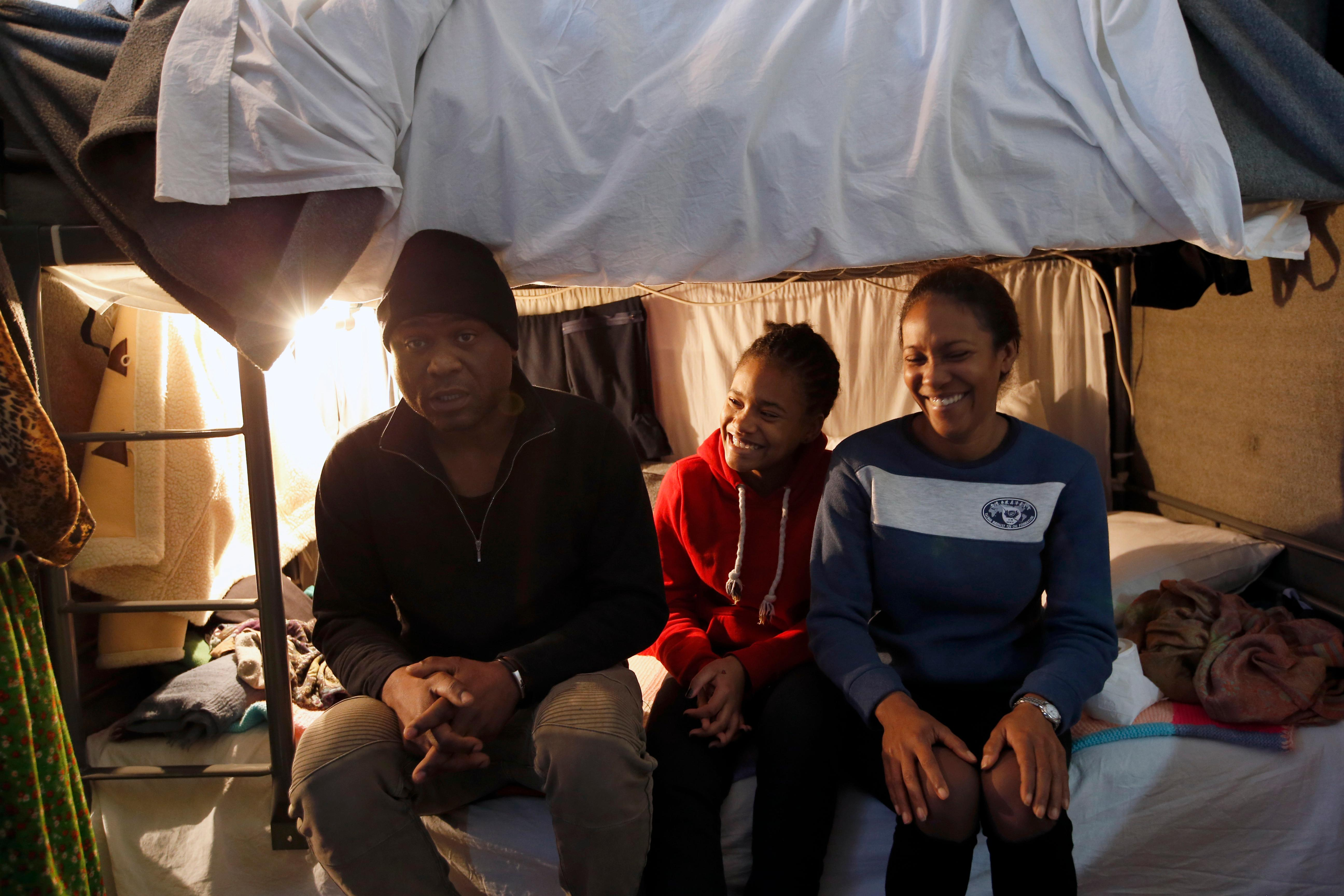 A Cuban migrant Michael Amor, left, with his wife Ingrid, right, and daughter Samira sitting in their room in the center for refugees in Sot, about 100 km west from Belgrade, Serbia, Thursday, Feb. 1, 2018.  Far away from sandy beaches and a balmy Caribbean breeze, a Cuban family huddles together in a cramped room of a Serbian refugee center, trying to figure out what to do next. They are part of an unlikely influx of Cuban migrants to the Balkans that began in 2015 before neighboring European Union countries sealed off their borders. Most Cuban migrants in Serbia say they had to make the trip after the U.S. revoked Cubans' special migration status last year.(AP Photo/Darko Vojinovic)
