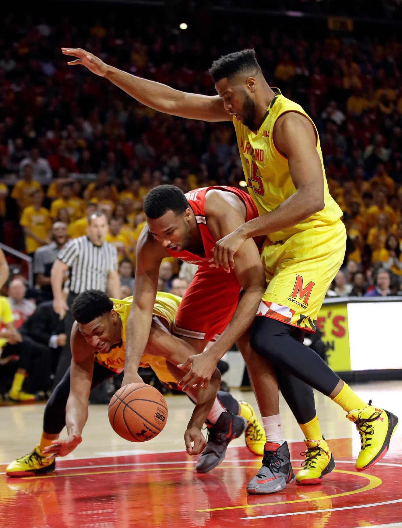 Ohio State center Trevor Thompson, center, becomes entangled with Maryland forwards Justin Jackson, left, of Canada, and Damonte Dodd as he tries to maintain possession of the ball in the first half of an NCAA college basketball game, Saturday, Feb. 11, 2017, in College Park, Md. (AP Photo/Patrick Semansky)