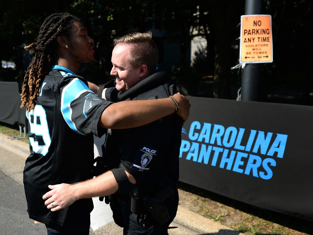 JaGerran Knight, of Charlotte, N.C., left, reaches out to hug a police officer at Bank of America Stadium, where people protest, prior to an NFL football game between the Minnesota Vikings and the Carolina Panthers in Charlotte, N.C., Sunday, Sept. 25, 2016. When the national anthem was played, the protesters all dropped to one knee as many NFL players have been doing for weeks to call attention to issues, including police shootings. (Jeff Siner/The Charlotte Observer via AP)