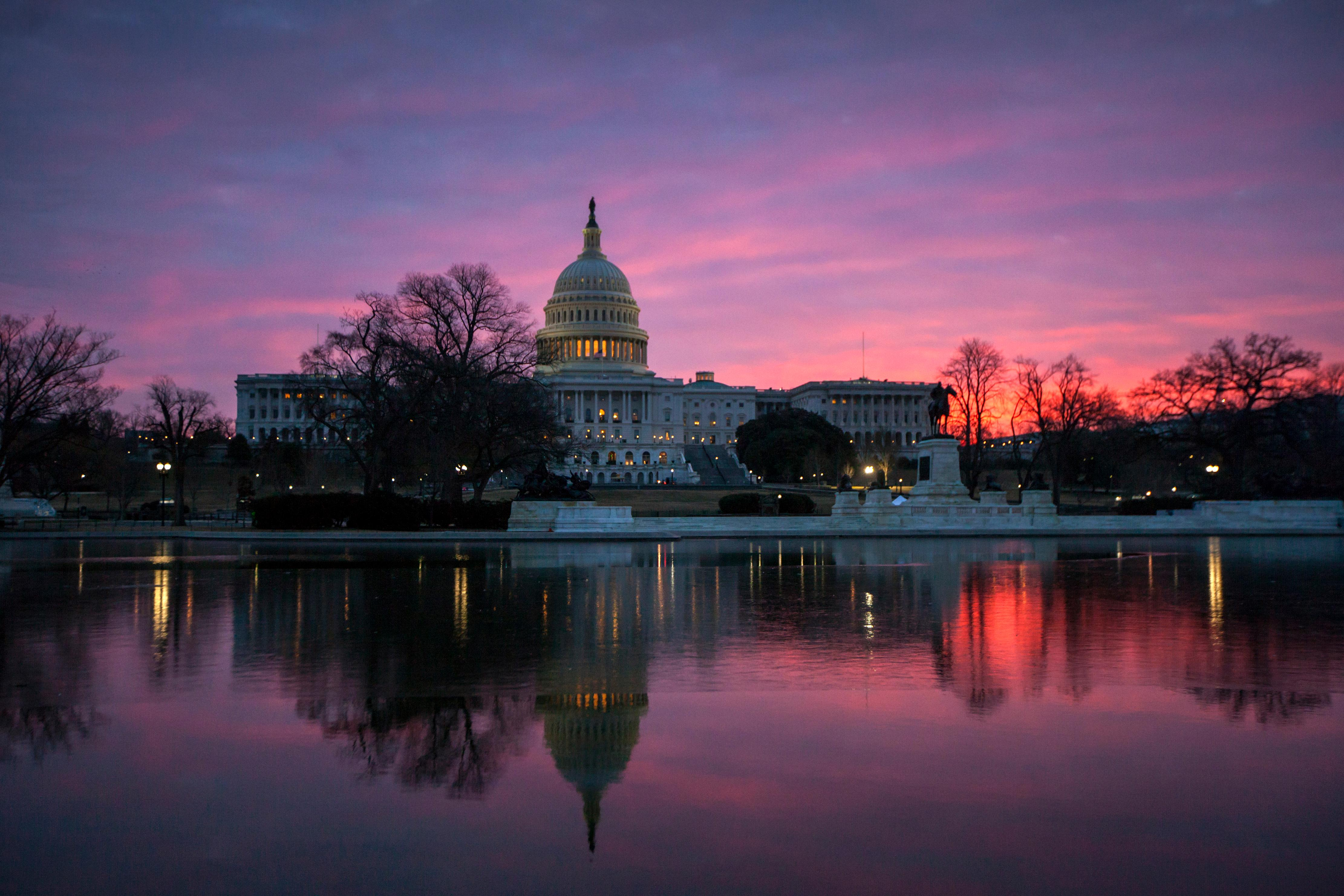 FILE - In this Feb. 6, 2018, file photo, dawn breaks over the Capitol in Washington. The once bipartisan drive to curb increases in health care premiums has devolved into a partisan struggle with escalating demands by each side. It's unclear they'll be able to reach an agreement. And the two parties may end up blaming each other this fall as states announce next year's inevitably higher insurance rates _ just weeks before Election Day on Nov. 6. (AP Photo/J. Scott Applewhite, File)