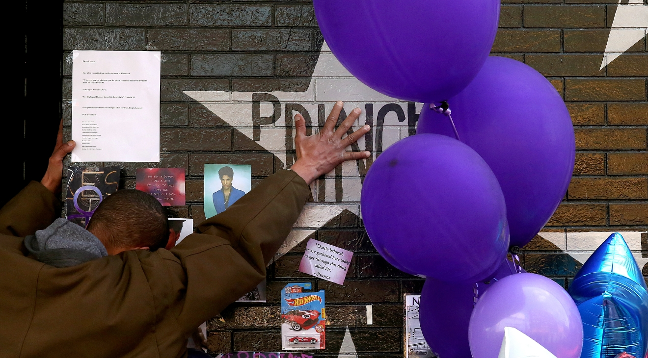 A mourner and fan touches the star for Prince on a wall at First Avenue where the singer often performed, Saturday, April 23, 2016, in Minneapolis. The pop superstar died Thursday at the age of 57. (Jim Gehrz /Star Tribune via AP)