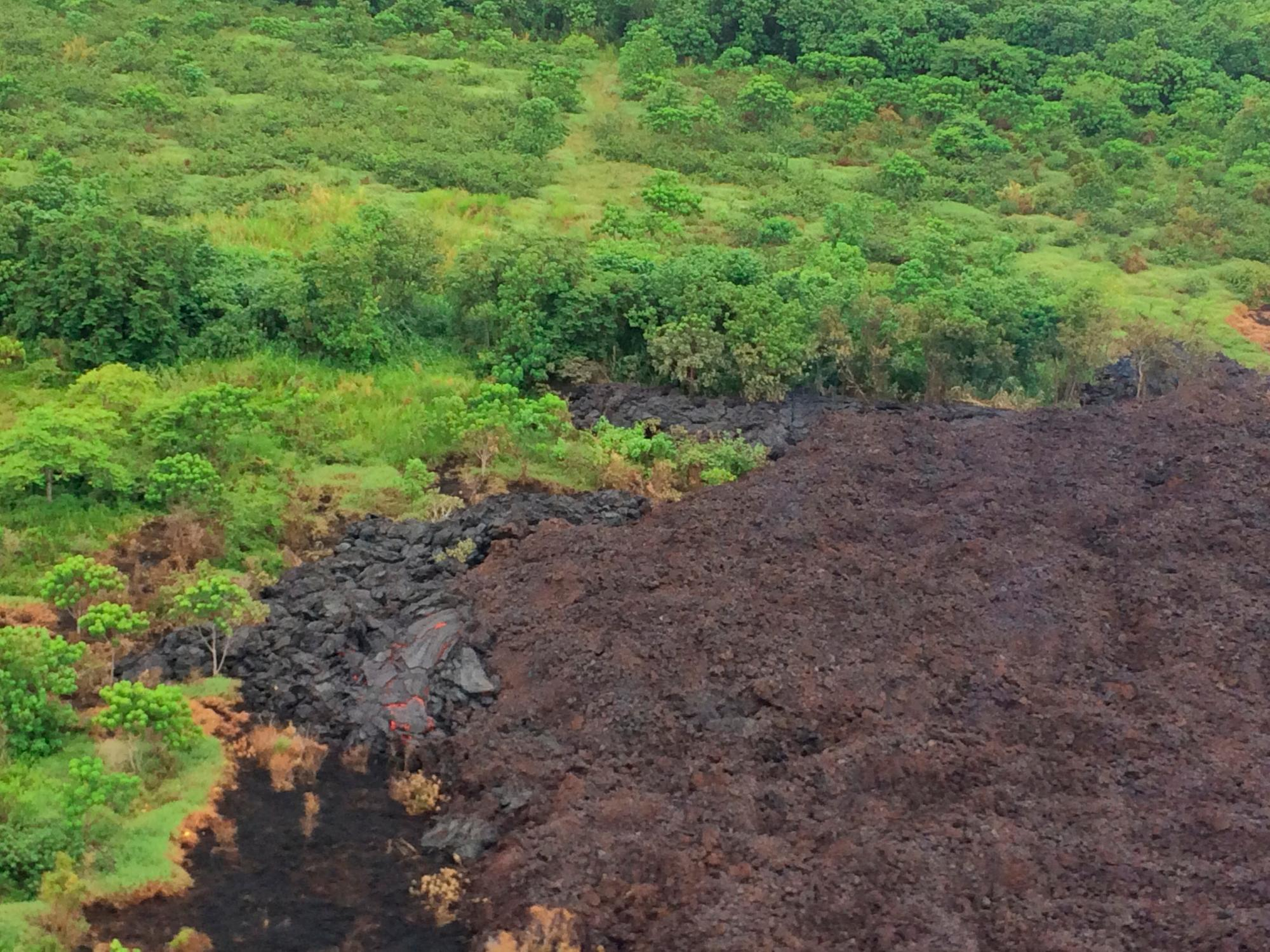 "This Thursday, May 17, 2018, aerial image released by the U.S. Geological Survey, shows Fissure 17 at about 07:00 a.m. HST., in Pahoa, Hawaii. The Fissure 17 flow front has slowed substantially with only small amounts of pasty ""toothpaste"" lava oozing out from the flow front. However lava continues to be erupted from the active fissure. This lava appears to be accumulating within the flow and has widened the flow margins slightly. (U.S. Geological Survey via AP)"