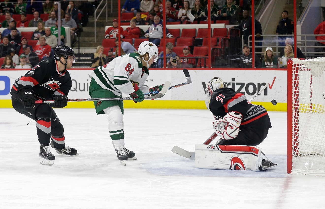 Minnesota Wild's Mikael Granlund (64), of Finland, shoots and scores against Carolina Hurricanes goalie Eddie Lack (31), of Sweden, as Hurricanes' Noah Hanifin (5) defends during the first period of an NHL hockey game in Raleigh, N.C., Thursday, March 16, 2017. (AP Photo/Gerry Broome)