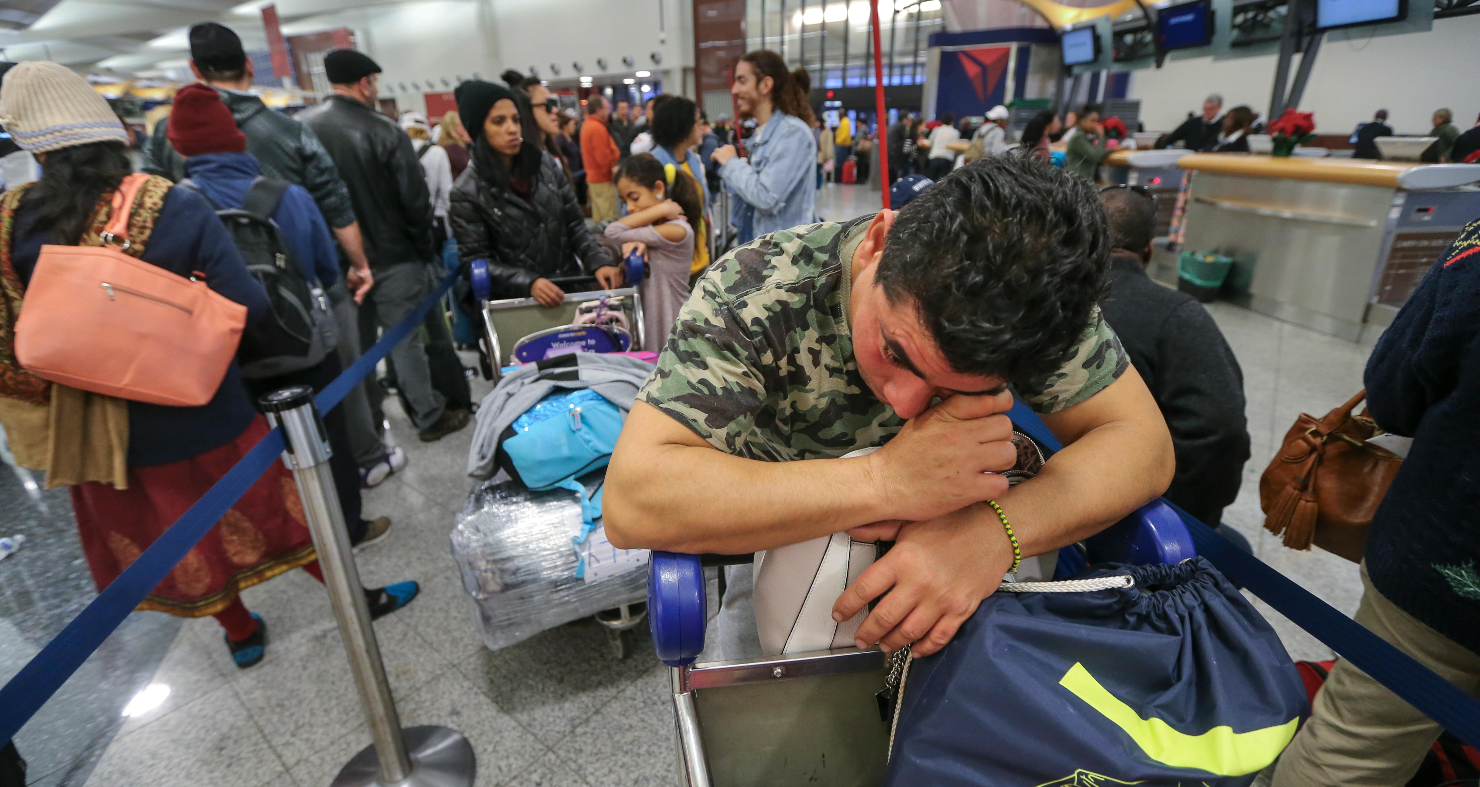 Alexis Canete rests on his luggage as he waits in the Delta ticket line to get back home to Cuba from his visit to Tennessee on Monday Dec. 18, 2017 at Hartsfield-Jackson International Airport in Atlanta, the day after a massive power outage brought operations to halt. Power was restored at the world's busiest airport after a massive outage Sunday afternoon that left planes and passengers stranded for hours, forced airlines to cancel more than 1,100 flights and created a logistical nightmare during the already-busy holiday travel season.  (John Spink/Atlanta Journal-Constitution via AP)
