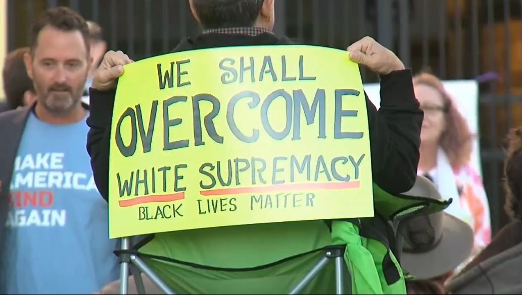 'We shall overcome' sign at Steve Bannon counter rally (WCIV)