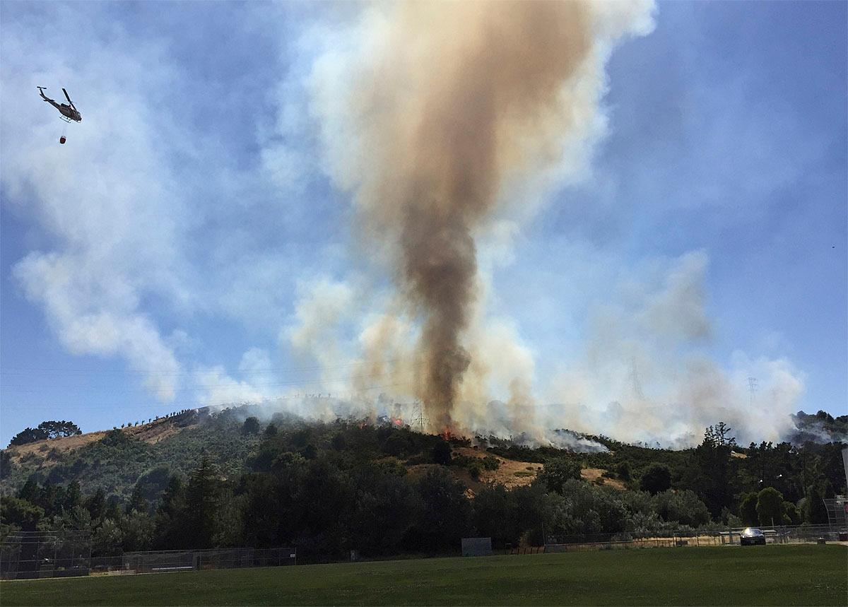 In this photo provided by Jocelyn Gecker, a helicopter flies over Moraga, Calif., as part of efforts Monday, June 19, 2017, to put out a grass fire that had burned through several acres behind Campolindo High School and was threatening homes. Contra Costa County fire officials say the blaze started Monday afternoon behind the high school. (Harrison Fuller via AP)