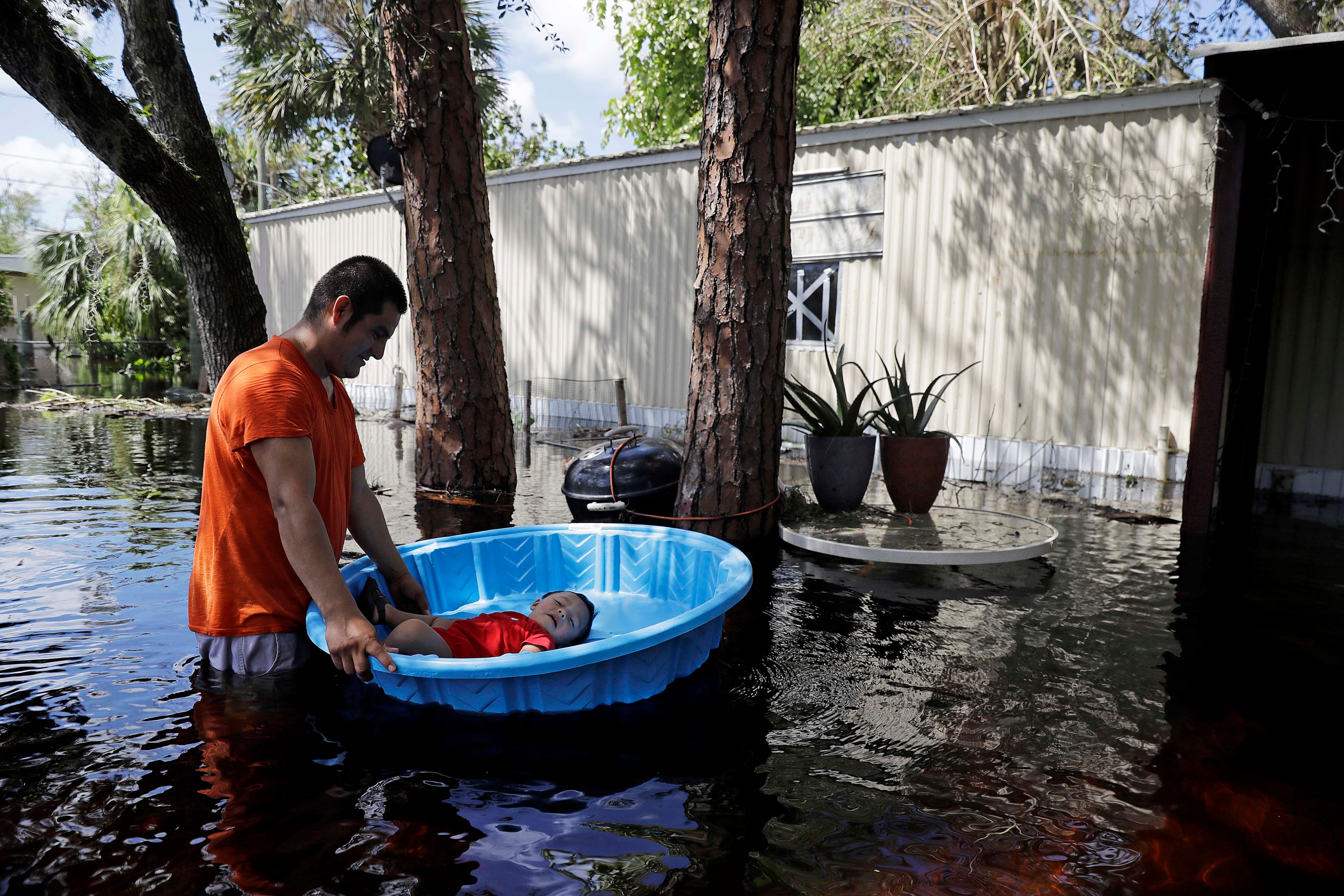 Jose Lopez floats his son Jose Jr, 1, in a splash pool as they retrieve belongings from their flooded home following Hurricane Irma in Bonita Springs, Fla., Tuesday, Sept. 12, 2017. (AP Photo/David Goldman)