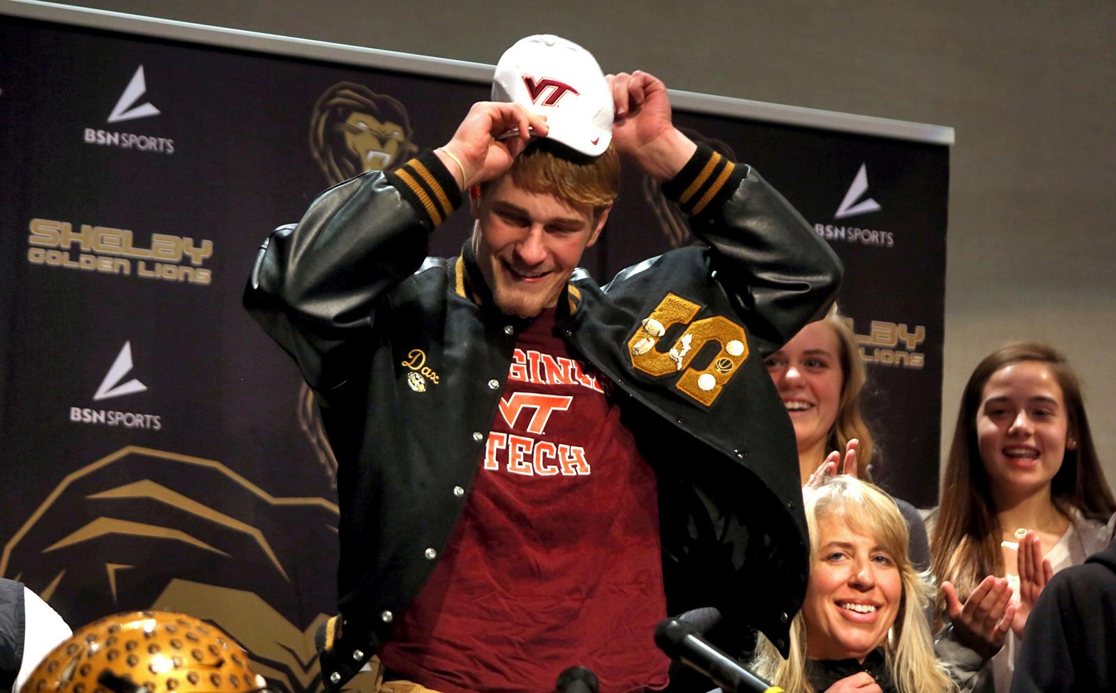 Shelby High School football player Dax Hollifield dons a Virginia Tech cap as he reveals his college decision during a signing day event at Shelby High School in Shelby, N.C. Wednesday, Feb. 7, 2018. (Brittany Randolph/The Star via AP)/The Star via AP)