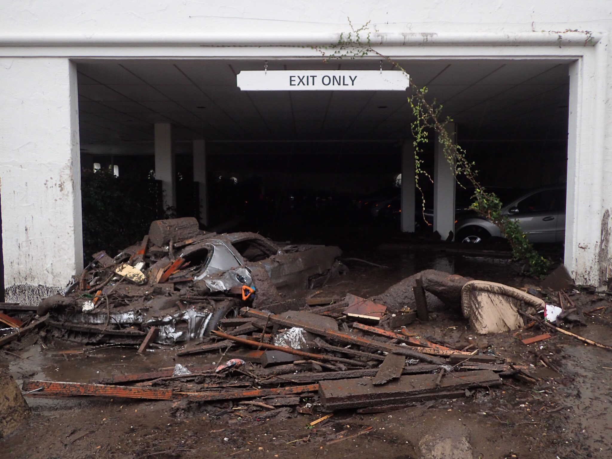 Damaged vehicles carried by mud flow and debris at the exit of the parking garage to the Montecito Inn (Photo: Mike Eliason / Santa Barbara County Fire)