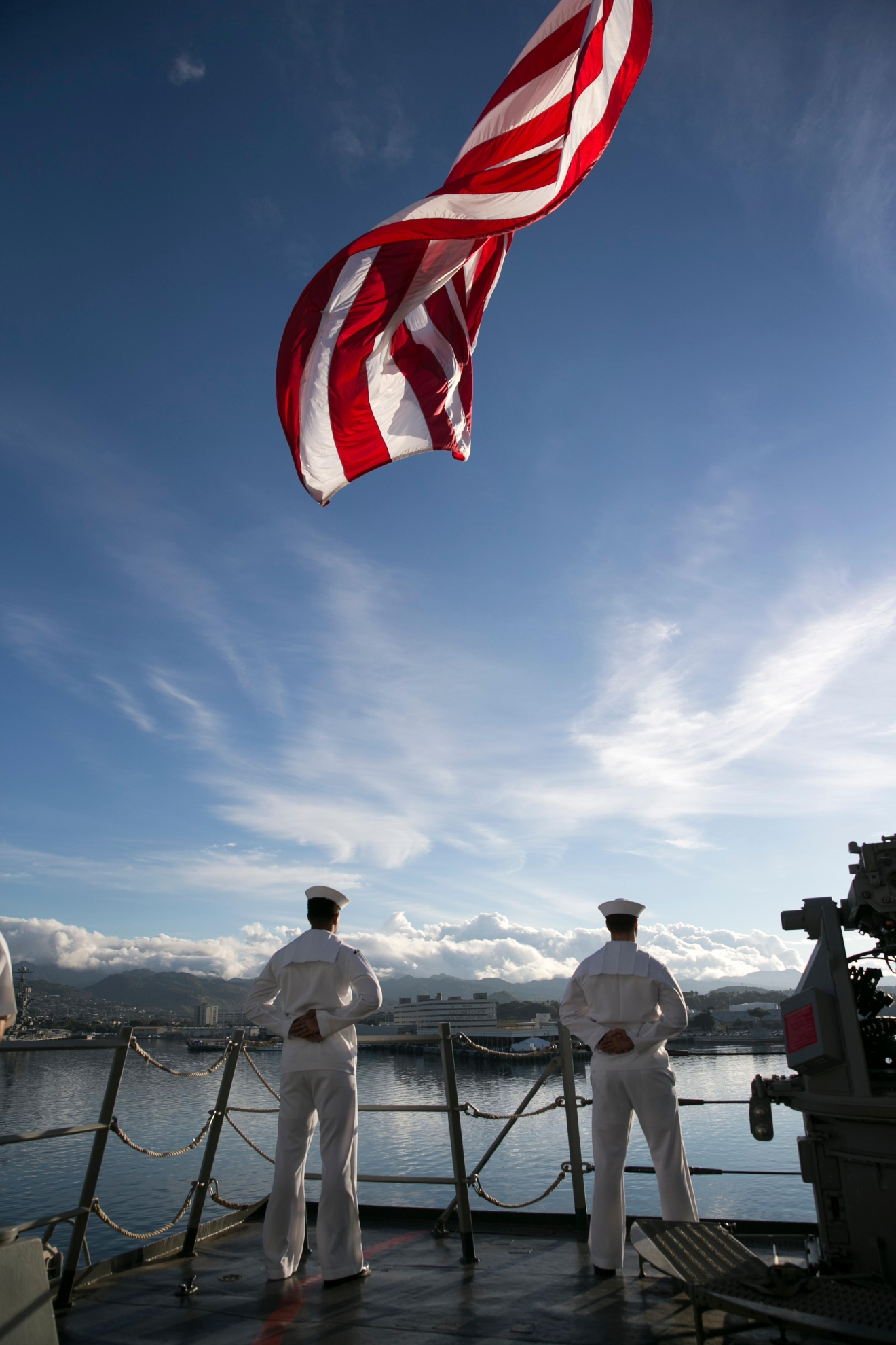 Navy sailors aboard the USS Halsey stand at parade rest as the ship passes by Kilo Pier at Pearl Harbor, Wednesday, Dec. 7, 2016, in Honolulu.  Survivors of the Japanese attack, dignitaries and ordinary citizens attended a ceremony at Kilo Pier to commemorate the 75th anniversary of the Japanese attack on the naval harbor.  (AP Photo/Marco Garcia)