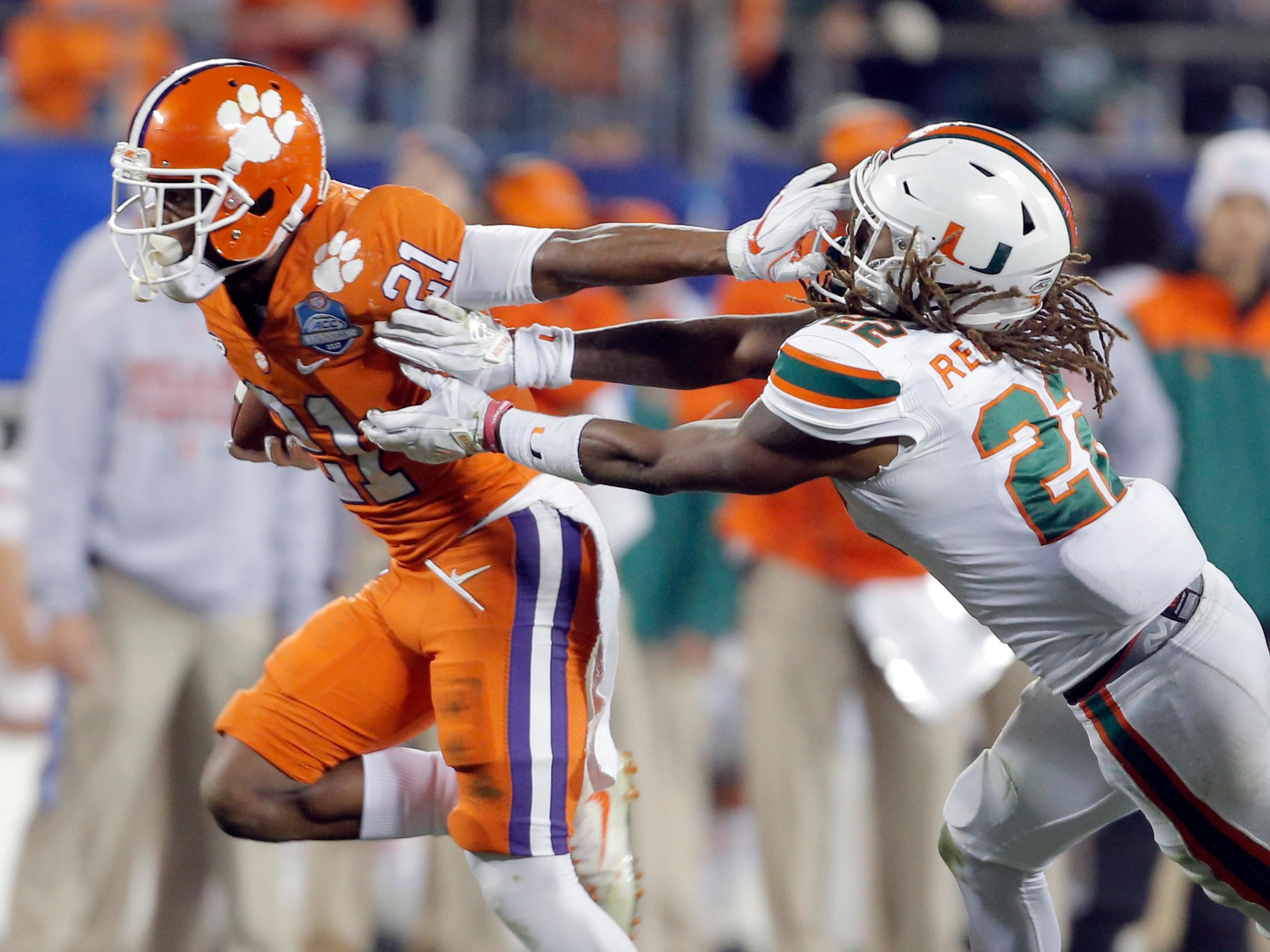 Clemson's Ray-Ray McCloud (21) pushes away from Miami's Sheldrick Redwine (22) during the second half of the Atlantic Coast Conference championship NCAA college football game in Charlotte, N.C., Saturday, Dec. 2, 2017. (AP Photo/Bob Leverone)