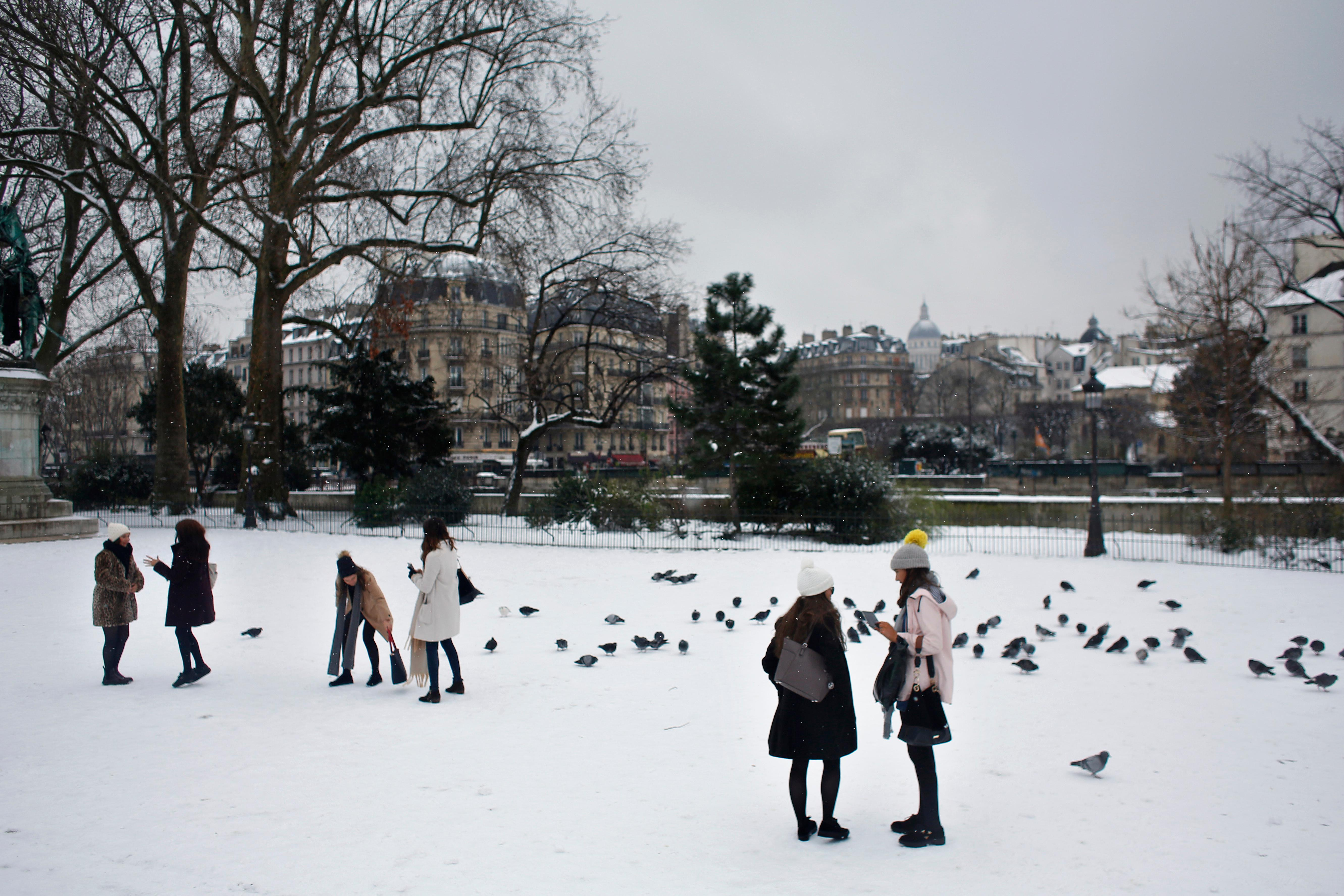 People stroll on the snow covered square in front of Notre Dame cathedral, in Paris, Friday, Feb. 9, 2018. Authorities are telling drivers in the Paris region to stay home as snow and freezing rain have hit a swath of France ill-prepared for the wintry weather. (AP Photo/Thibault Camus)