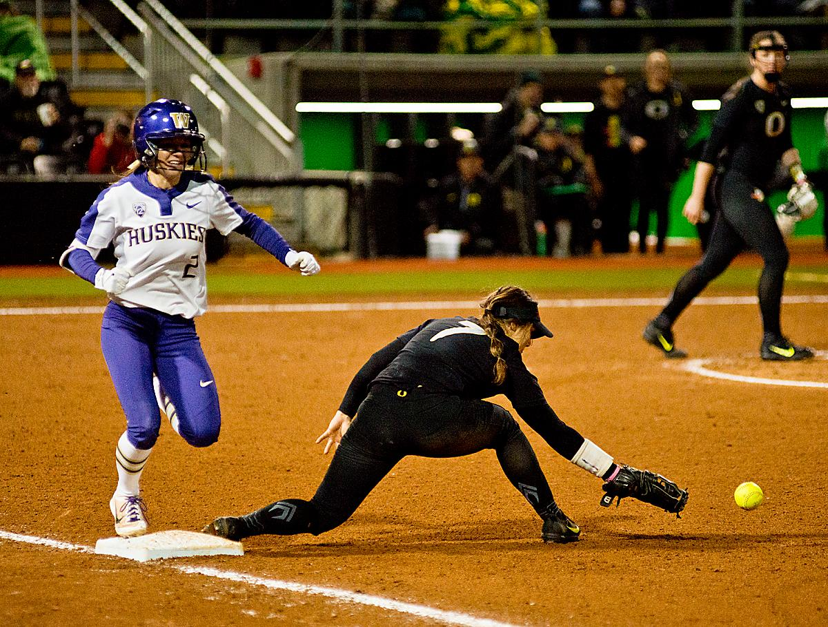 Huskies Trysten Melhart (#2) is safe at first as Ducks Mia Camuso can't hold on to the ball. In Game Two of a three-game series, the University of Oregon Ducks softball team defeated the University of Washington Huskies 4-1 Friday night in Jane Sanders Stadium. Danica Mercado (#2), Alexis Mack (#10) and Mia Camuso (#7) all scored in the win, Mack twice. The Ducks play the Huskies for the tie breaker on Saturday with the first pitch at noon. Photo by Dan Morrison, Oregon News Lab