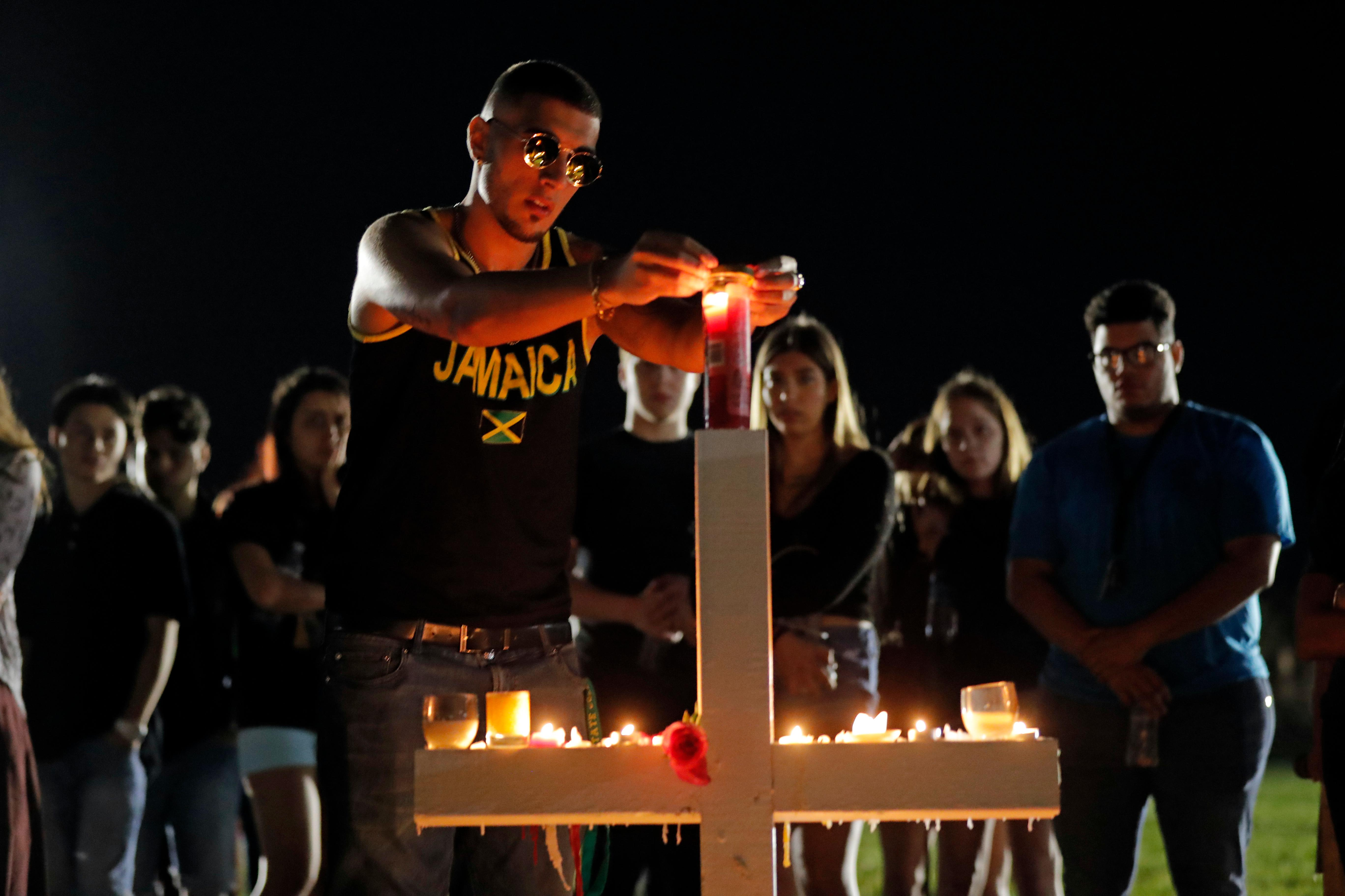 Joey Kandil, 18, a recent graduate of Marjory Stoneman Douglas High School, places a ring around a candle on one of seventeen crosses, after a candlelight vigil for the victims of the Wednesday shooting at the school, in Parkland, Fla., Thursday, Feb. 15, 2018. Nikolas Cruz, a former student, was charged with 17 counts of premeditated murder on Thursday. (AP Photo/Gerald Herbert)