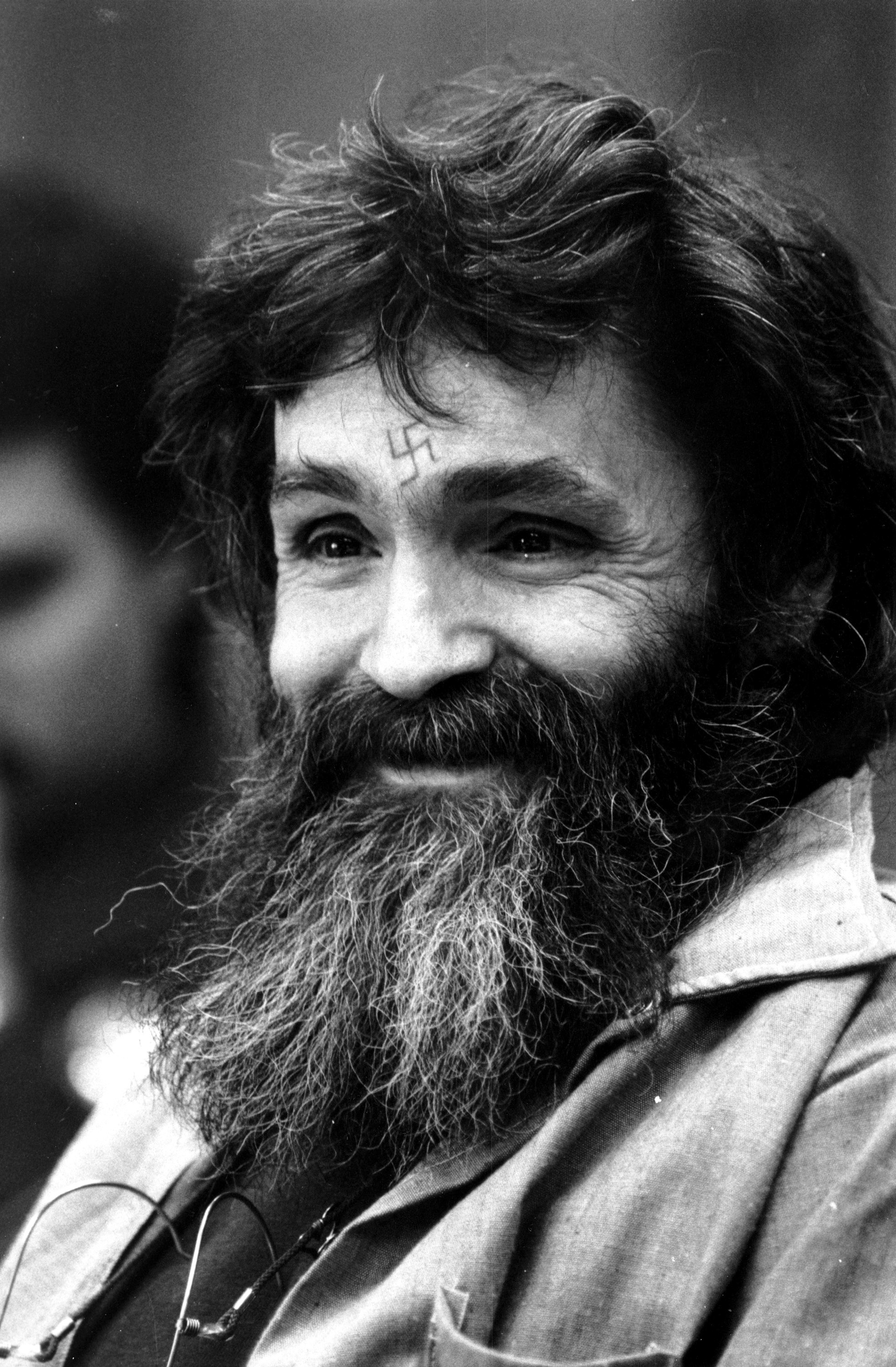 FILE - In this Feb. 4, 1986, file photo, convicted murderer Charles Manson looks towards the parole board in San Quentin, Calif. Authorities say Manson, cult leader and mastermind behind 1969 deaths of actress Sharon Tate and several others, died on Sunday, Nov. 19, 2017. He was 83.(AP Photo/Eric Risberg, File)