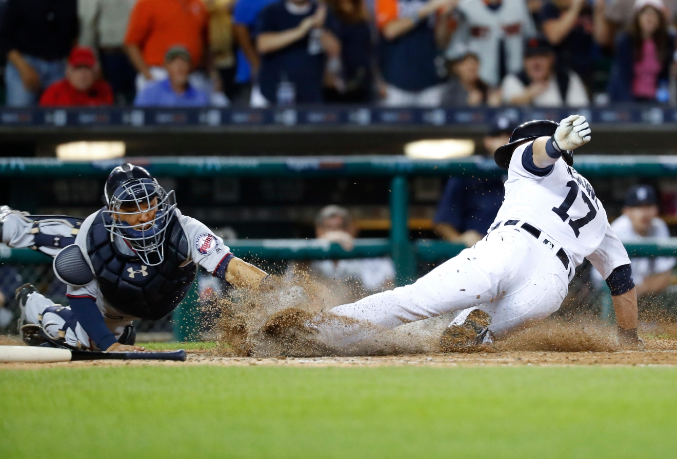 Detroit Tigers' Andrew Romine (17) slides safely before the tag of Minnesota Twins catcher Kurt Suzuki at home plate to score on a Jose Iglesias double in the seventh inning of a baseball game in Detroit, Monday, Sept. 12, 2016. Iglesias advanced to third on the throw. (AP Photo/Paul Sancya)