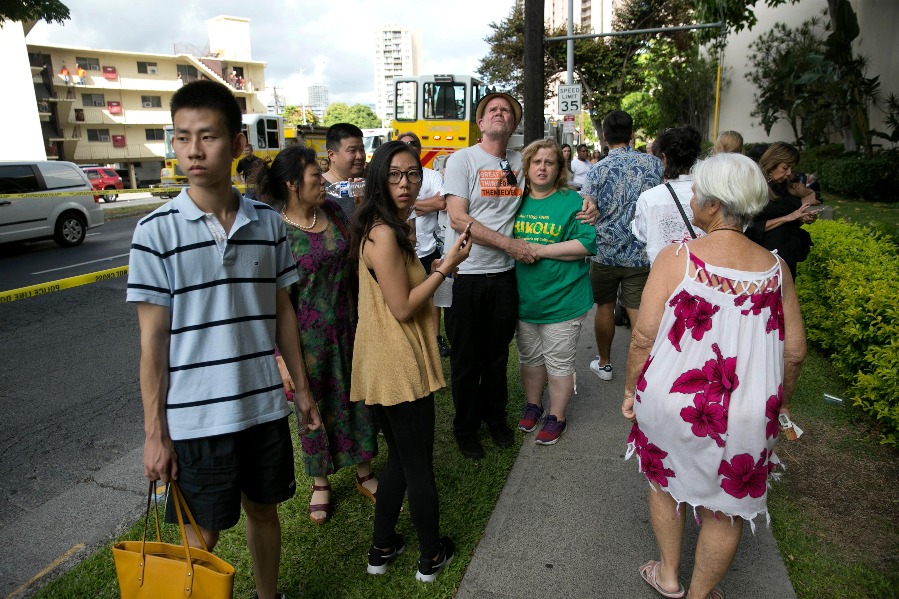 Onlookers stand on a sidewalk as a fire burns at the Marco Polo apartment complex, Friday, July 14, 2017, in Honolulu. (AP Photo/Marco Garcia))