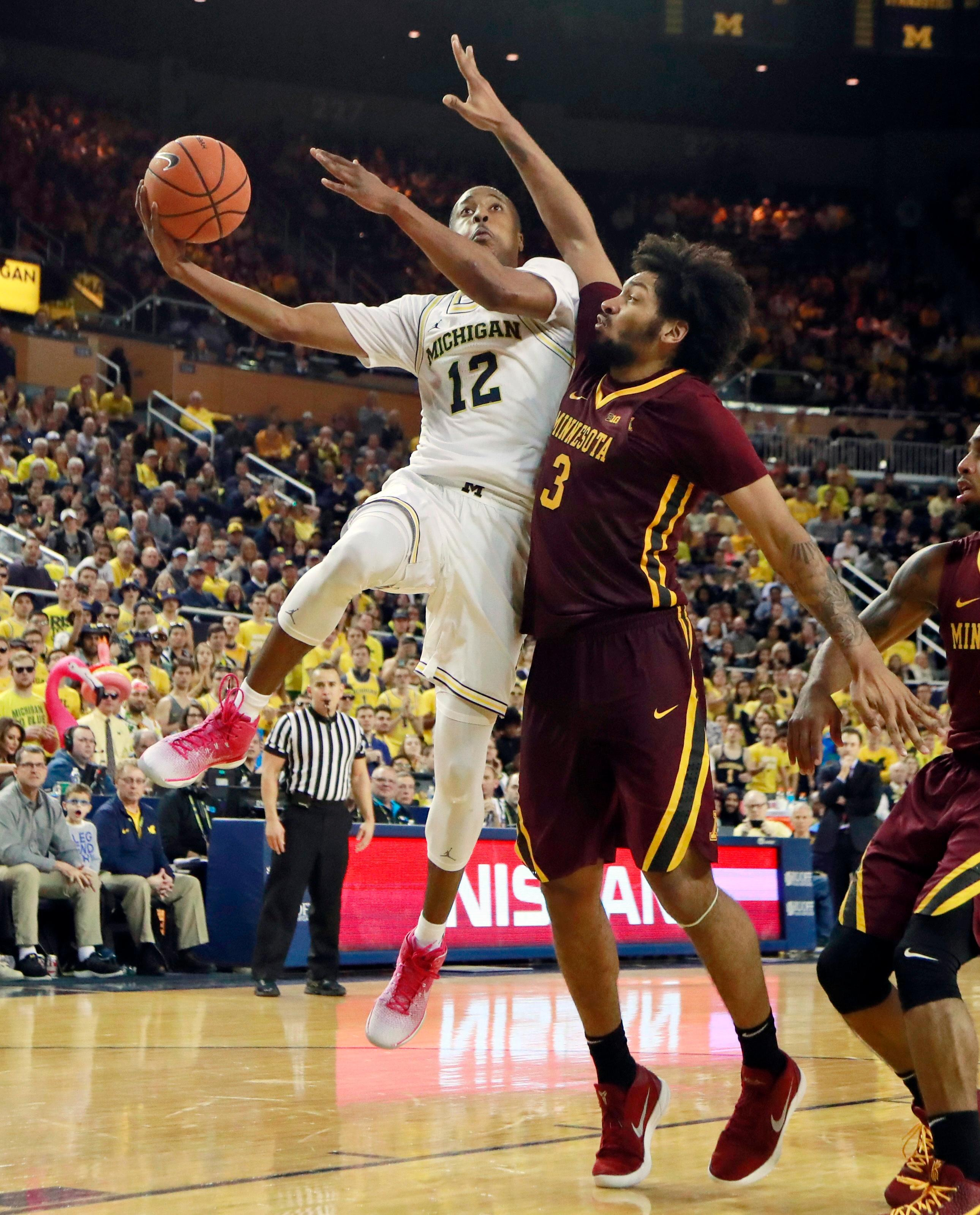 Michigan guard Muhammad-Ali Abdur-Rahkman (12) shoots as Minnesota forward Jordan Murphy (3) defends during the second half of an NCAA college basketball game, Saturday, Feb. 3, 2018, in Ann Arbor, Mich. (AP Photo/Carlos Osorio)