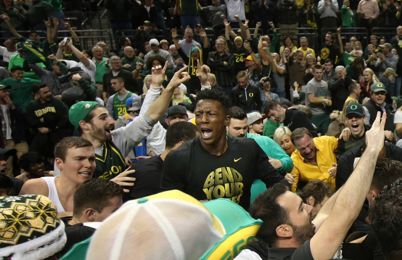 Oregon's Casey Benson, left, and Kavell Bigby-Williams, center, celebrate with fans as they storm the court after teammate's Dillon Brook's game winning shot over UCLA in an NCAA college basketball game Wednesday, Dec. 28, 2016, in Eugene, Ore. (AP Photo/Chris Pietsch)