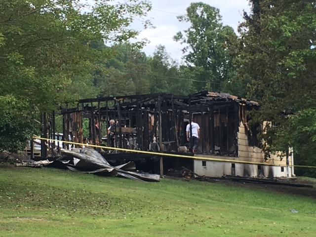 A house fire broke out late Thursday night at a home connected to three suspects charged with felony accessory after the fact to first-degree murder in the Phillip Stroupe II case. (Photo credit: WLOS staff)