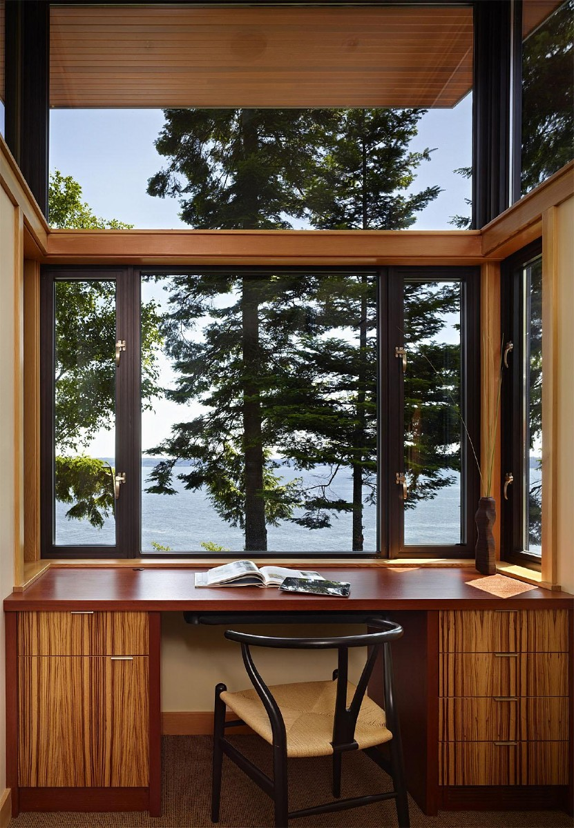 This Port Ludlow modern home has beautiful waterfront views of Hood Canal and the home office space shows them off beautifully! This project was completed by FINNE Architects.  (Image: Port Ludlow / Porch.com)