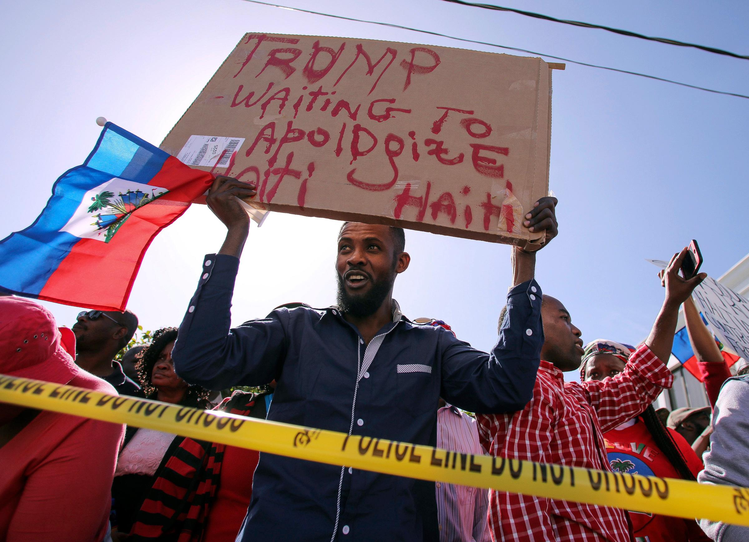 Haitian community members protest near President Donald Trump's Mar-a-Lago estate Monday, Jan. 15, 2018, in West Palm Beach, Fla. Trump is defending himself anew against accusations that he is racist, this time after recent disparaging comments about Haiti and African nations. The group said they were there to demand an apology from the Trump. (Damon Higgins/Palm Beach Post via AP)