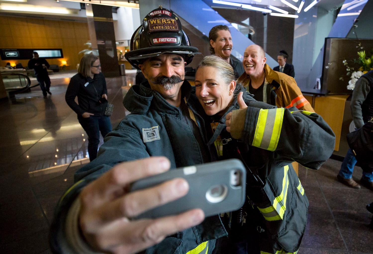 Rich Brown, lead ambassador and firefighter from Boise, Idaho, takes a selfie with a Seattle firefighter before climbing the 69 floors of the Columbia Tower to train for the Scott Firefight Stairclimb that benefits the Leukemia & Lymphoma Society. 2,000 firefighters will climb the 69 floors (1,356 stairs!) on Sunday. To donate to this cause, please visit www.firefighterstairclimb.org. (Sy Bean / Seattle Refined)