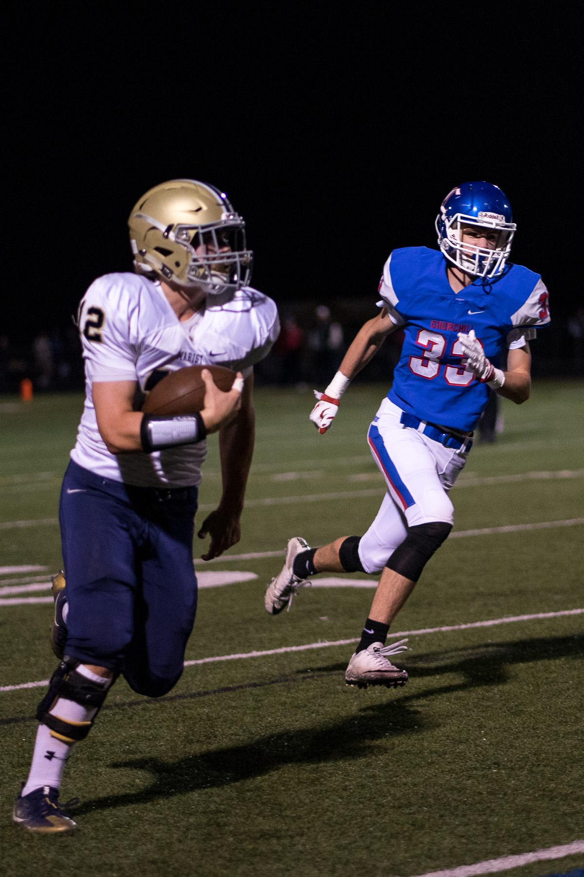 Marist Spartans running back Mitchell Hopkins (#12) runs the ball while being pressured by Churchill's Mitchell Whittier (#33). The Churchill Lancers defeated the Marist Catholic Spartans 41 - 20 at Churchill High School on Friday, October 6. Photo by Kit MacAvoy, Oregon News Lab