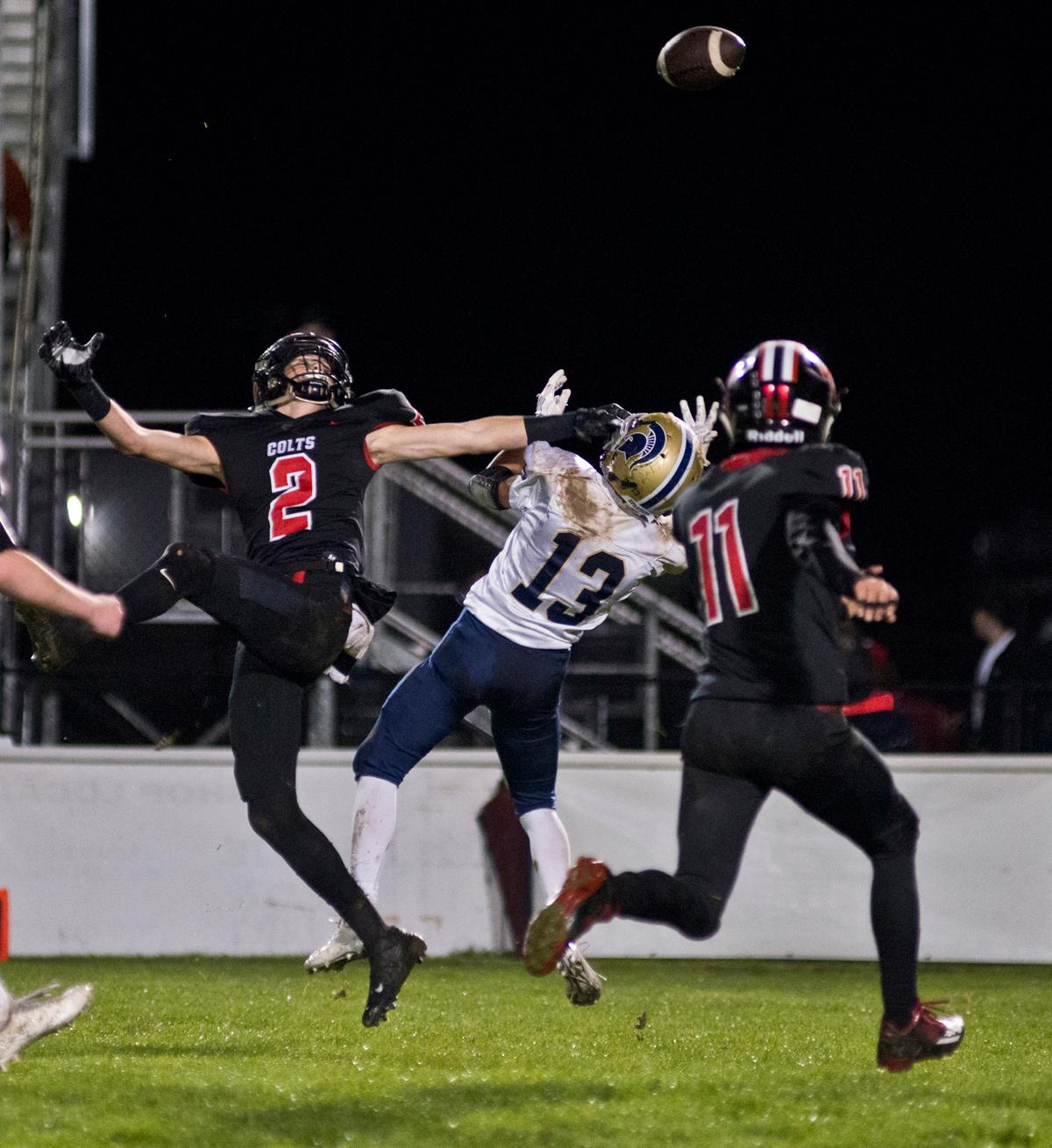 Thurston Colts defensive back D.J. Stedman (#2), Marist Spartans wide receiver Hagan Stephenson (#13) and Colts defensive back Trevor Duran (#11) all fight for a passed ball. Thurston defeated Marist 50 to 14 to seal the second position in their conference. Photo by Dan Morrison, Oregon News Lab