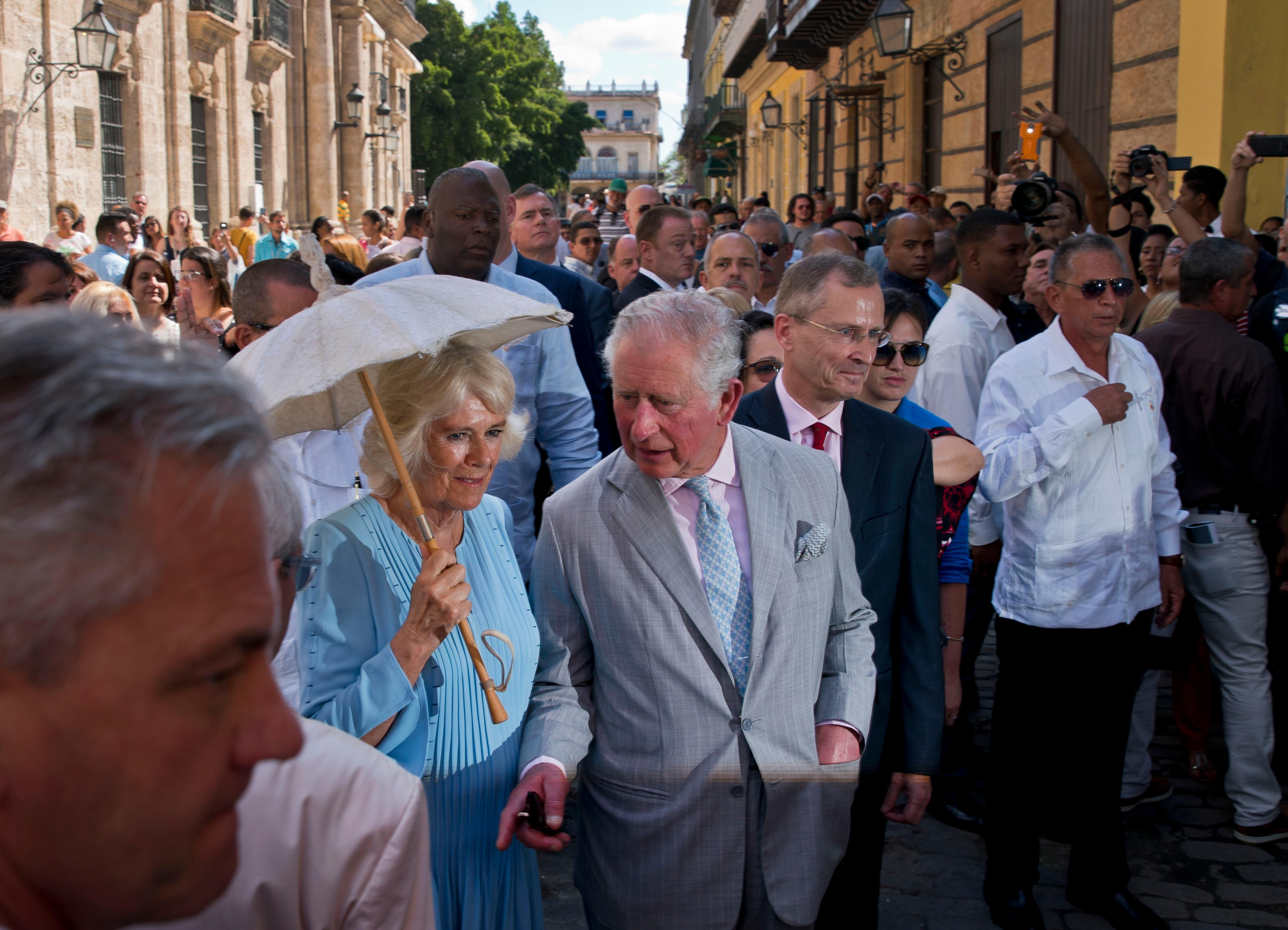Britain's Prince Charles, the Prince of Wales, center, and his wife Camilla, Duchess of Cornwall, take a guided tour of the historical area of Havana, Cuba, Monday, March 25, 2019. The royal couple began the first official trip to Cuba by the British royal family on Sunday, in a pomp-filled display of disagreement with the Trump administration's strategy of economically isolating the communist island. (AP Photo/Ramon Espinosa)