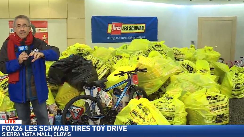Kopi with the stacks of toys donated to the Les Schwab Toy Drive (2016)