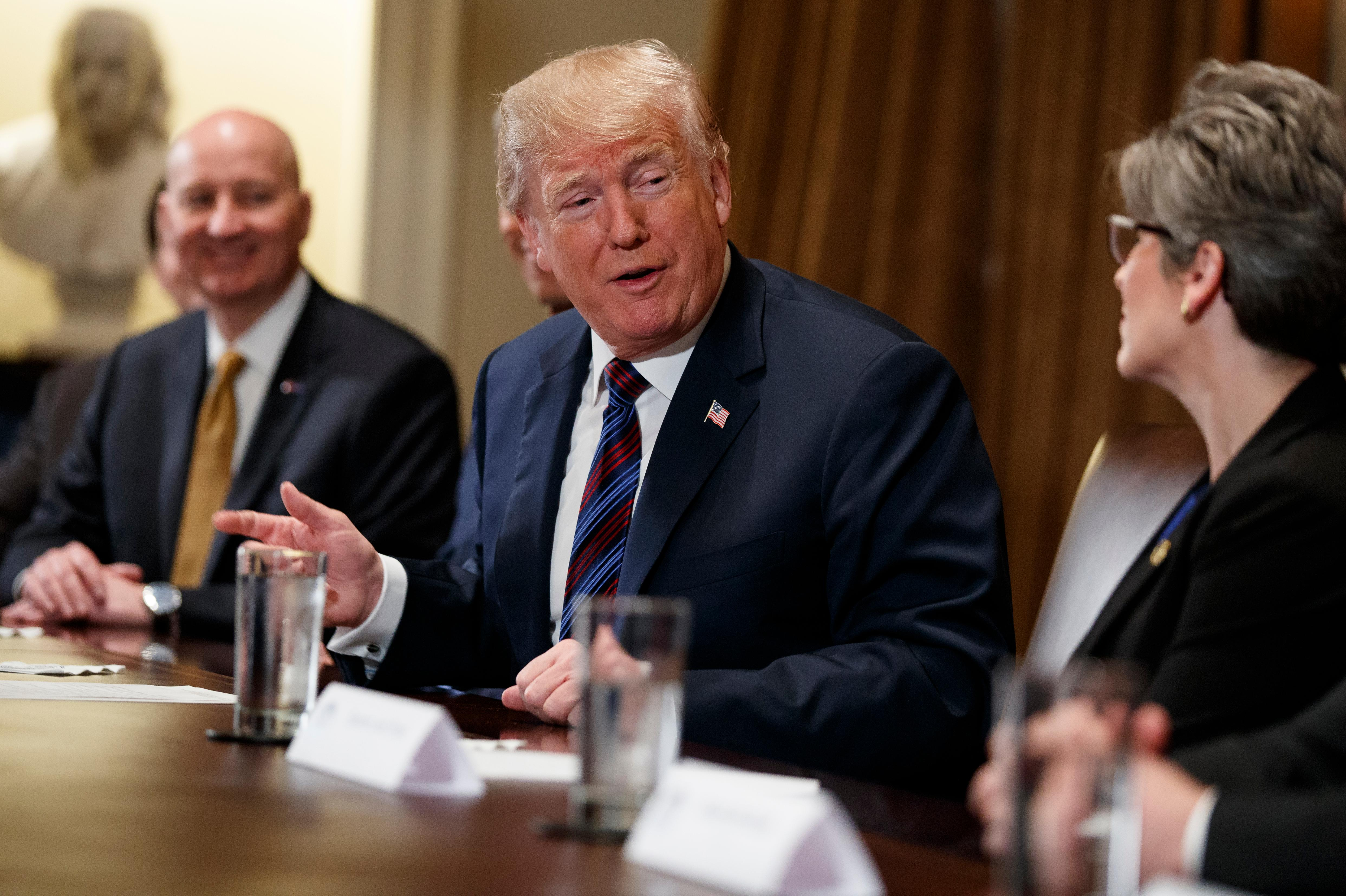 Gov. Pete Ricketts, R-Neb., left, listens as President Donald Trump speaks to Sen. Joni Ernst, R-Iowa, during a meeting with governors and lawmakers in the Cabinet Room of the White House, Thursday, April 12, 2018, in Washington. (AP Photo/Evan Vucci)