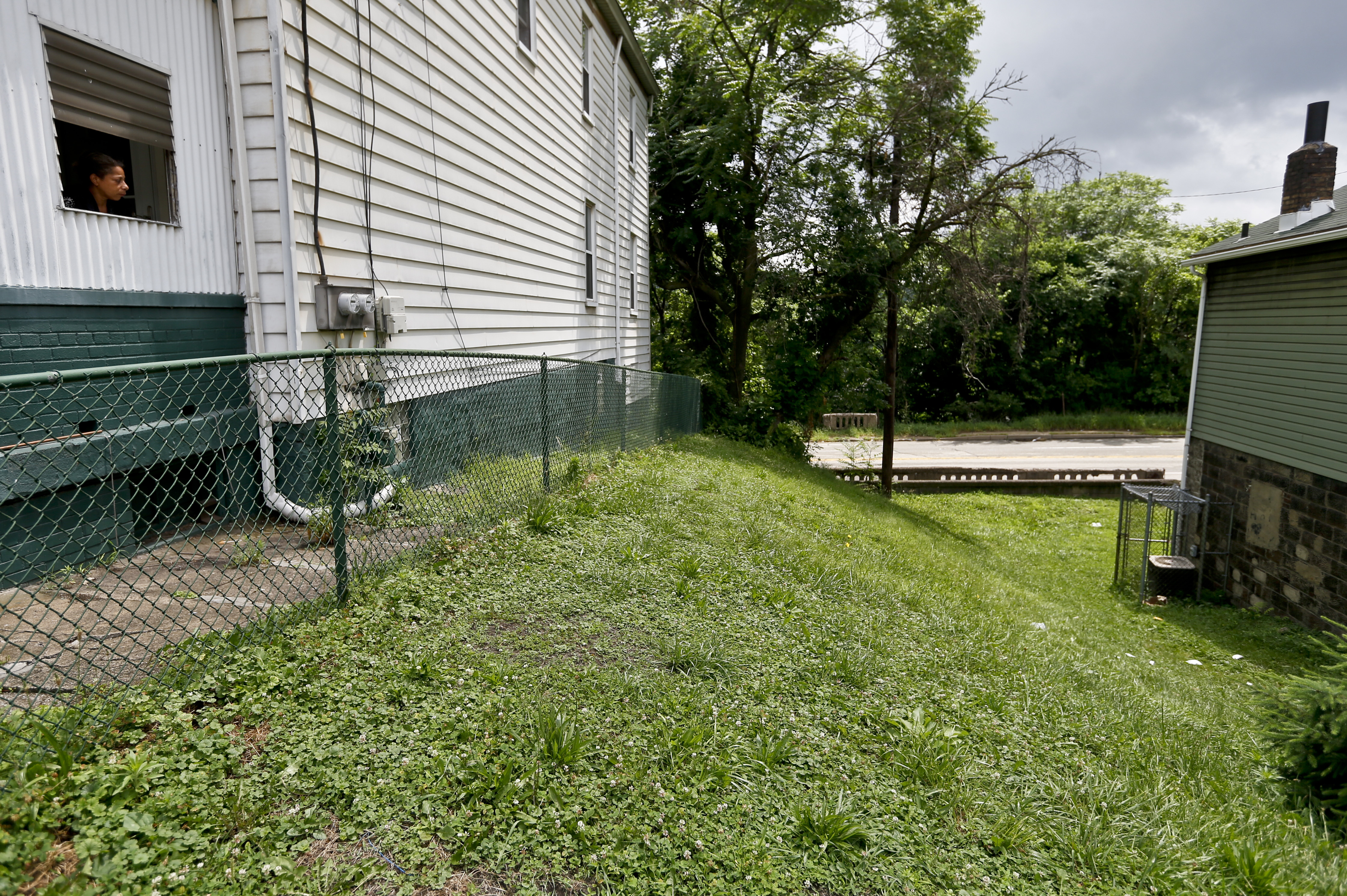 Debra Jones, left, looks over the lot on Wednesday, June 20, 2018, in East Pittsburgh, Pa., where she says she saw a police officer fatally shoot a 17-year-old boy just seconds after he fled from a traffic stop during a confrontation late the night before. (AP Photo/Keith Srakocic)
