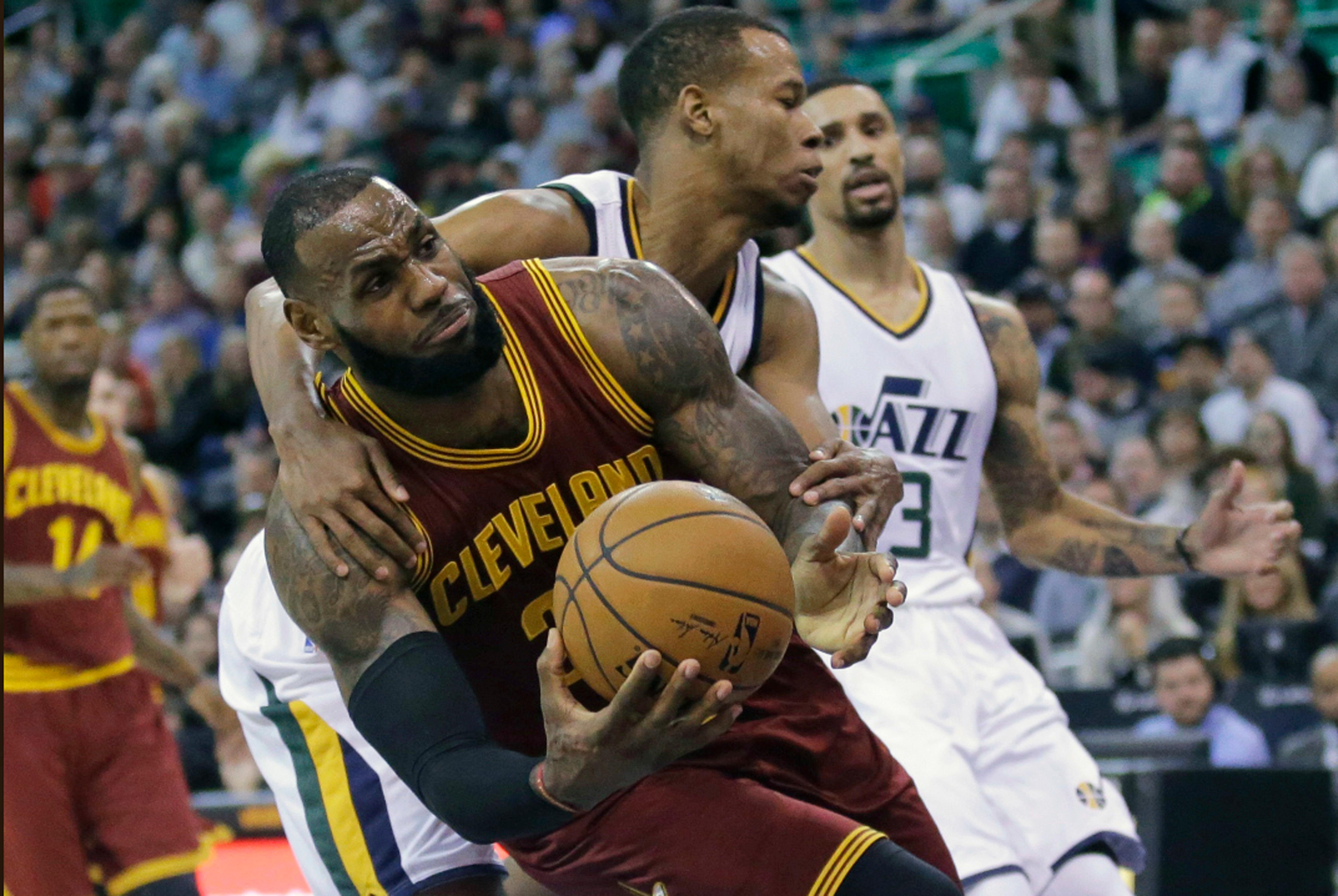 Utah Jazz guard Rodney Hood, rear, fouls Cleveland Cavaliers forward LeBron James, left, as he goes to the basket in the first half during an NBA basketball game Tuesday, Jan. 10, 2017, in Salt Lake City. (AP Photo/Rick Bowmer)